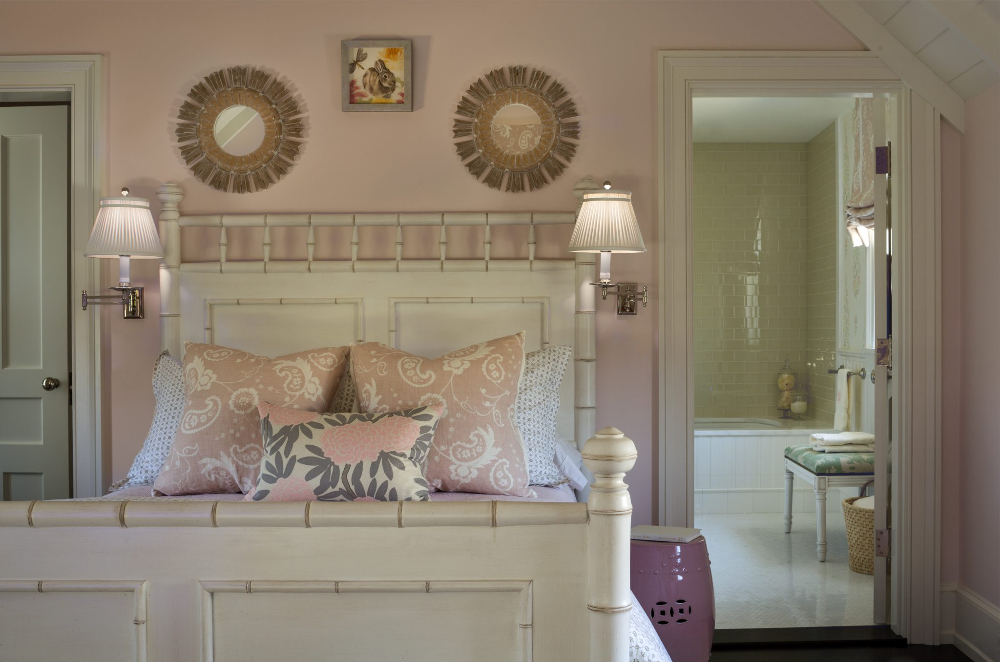 Feminine bed with pink garden stool, wall sconces and Asian-inspired florals by SLC Interiors