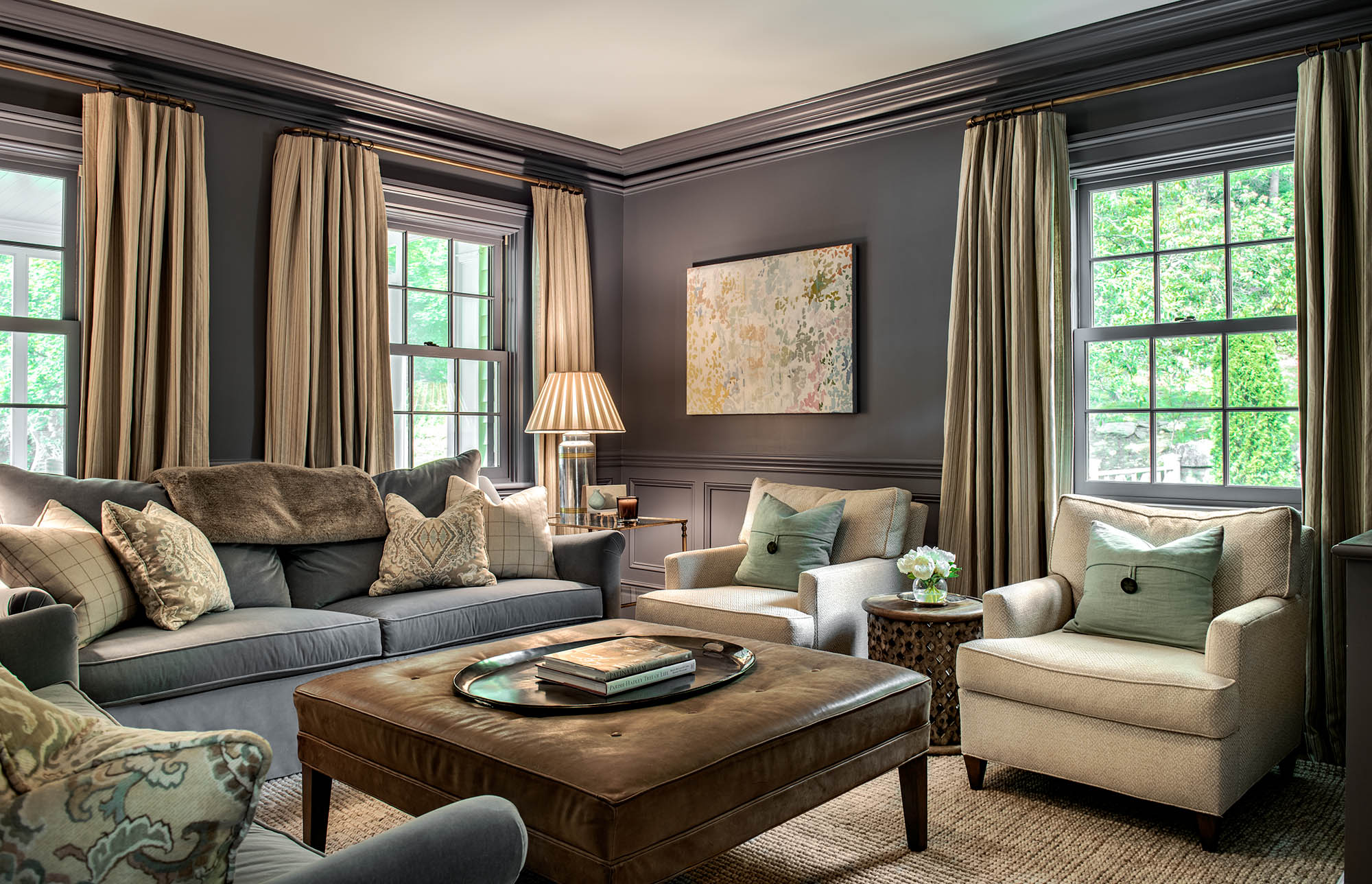 """Benjamin Moore's Montpelier (AF-555)  """"This room does not get much sunlight, so we decided to embrace the lack of light and create a cozy and intimate library and television room for our clients. The blue gray paint color, which is used on the wainscot, walls, and trim, coordinates with the velvet upholstery on the sofa and helps to create a comfortable yet elegant space. It is a perfect room for relaxing in with a glass of wine, a good book, or a favorite movie after a long week!""""  Elizabeth Brush Saypol & Elise Morrissey, of Morrissey Saypol Interiors"""
