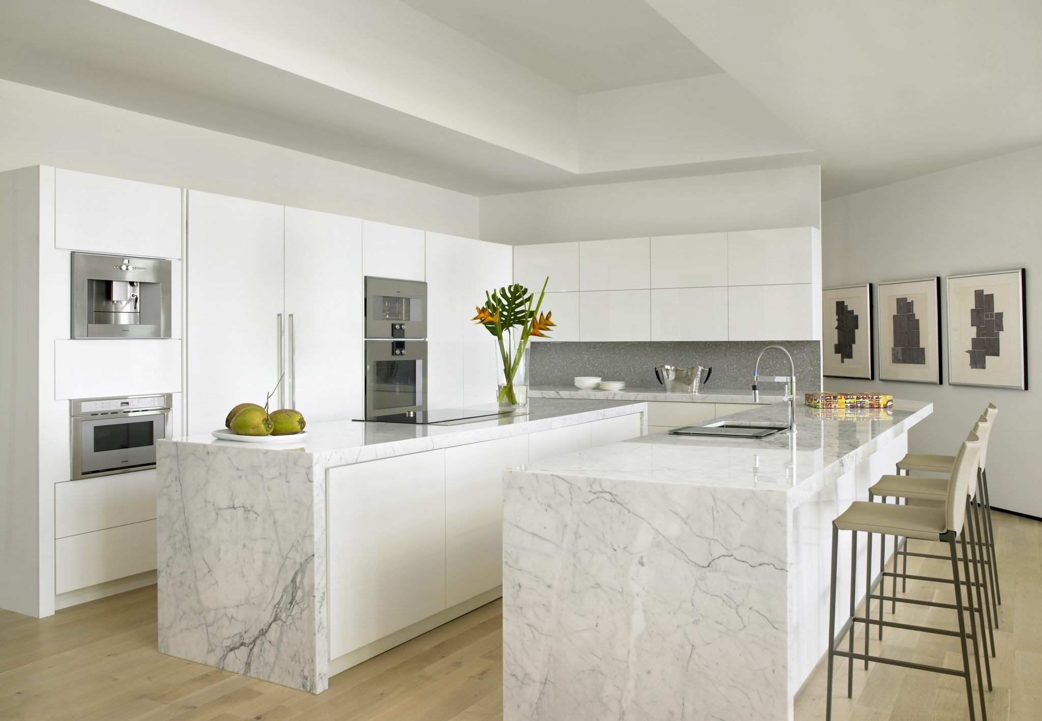 The kitchen's all-white theme—including cabinetry keeps the space as light as a cloud. The Carrara marble countertops and pencil-legged barstools continue the modern scheme. By Michael Wolk Design Associates