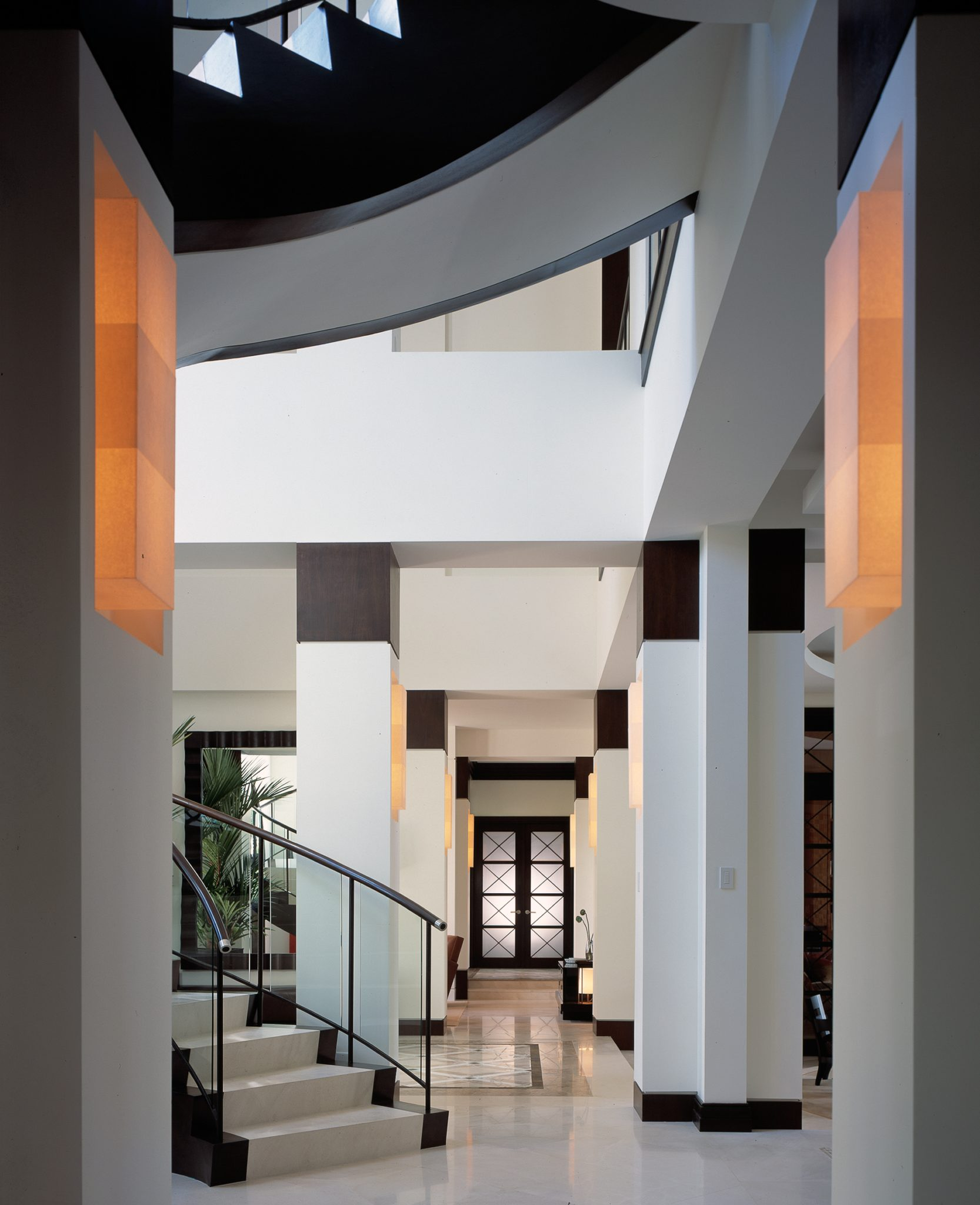 A sculptural foyer own white with glass, wood and metal details, captivates. by Alene Workman Interior Design