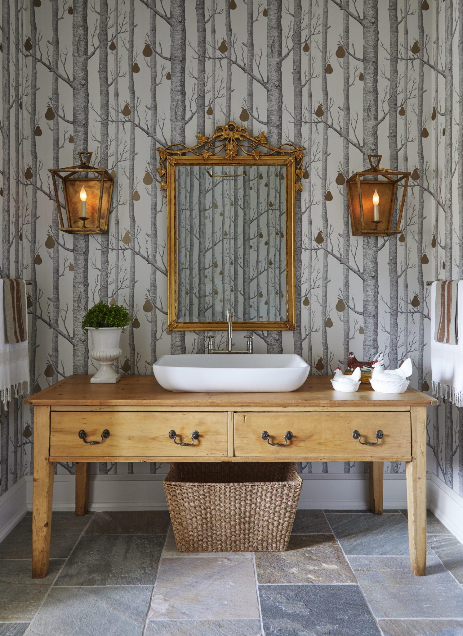 Rustic chic bathroom with tree printed wallpaper, lantern sconces, wooden vanity by Elizabeth Drake