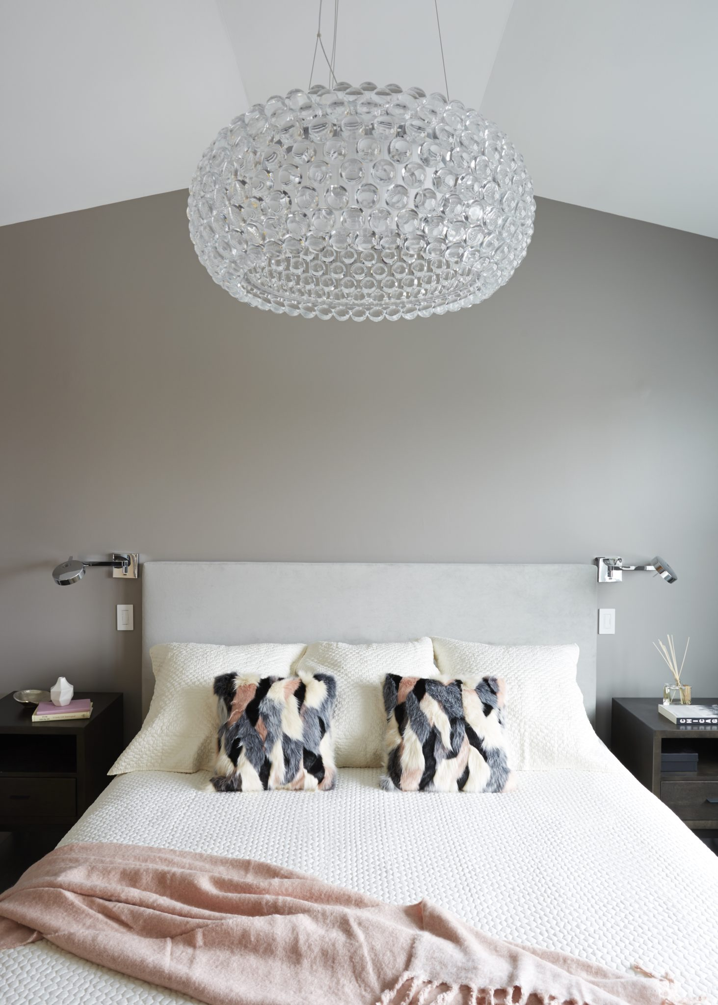 Pink, gray and cream hues in a modern condo master bedroom featuring a lucite pendant and sconces by Maren Baker Design