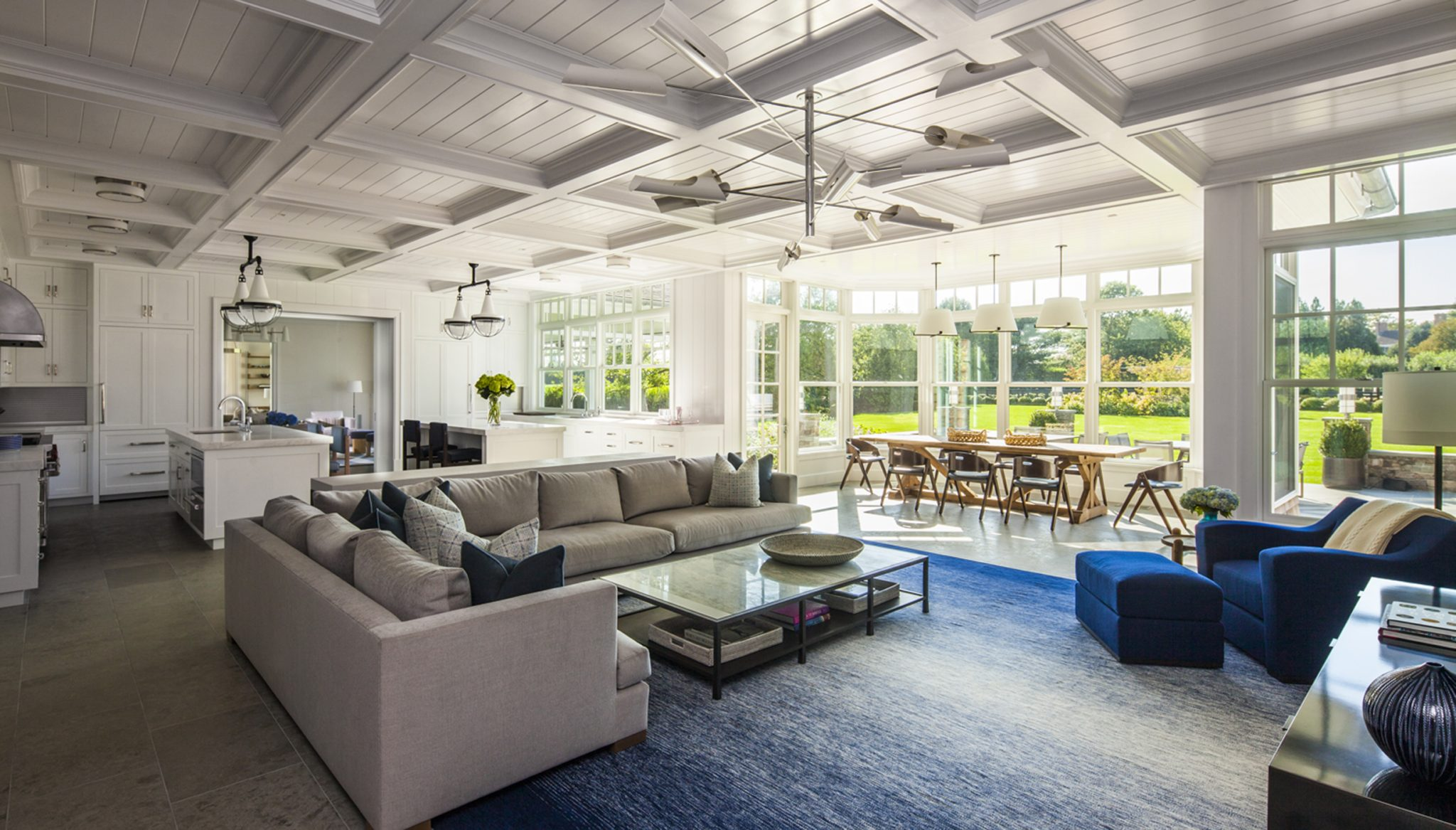 Hamptons residence - coffered ceiling in a family room that's open to kitchen and dining area. By Stephens Design Group