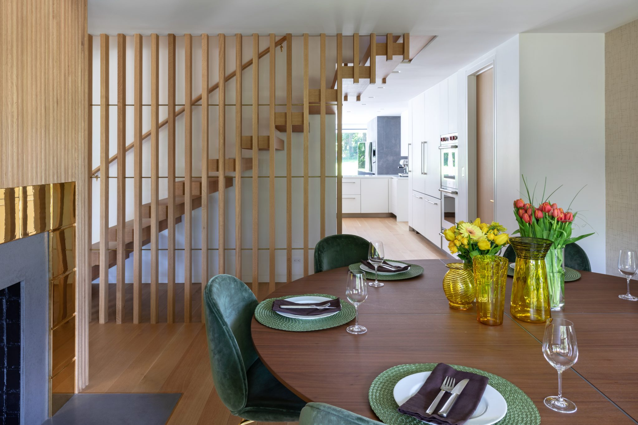 Dining room with wood paneled wall and a view to the floating white oak stair by Alisberg Parker Architects