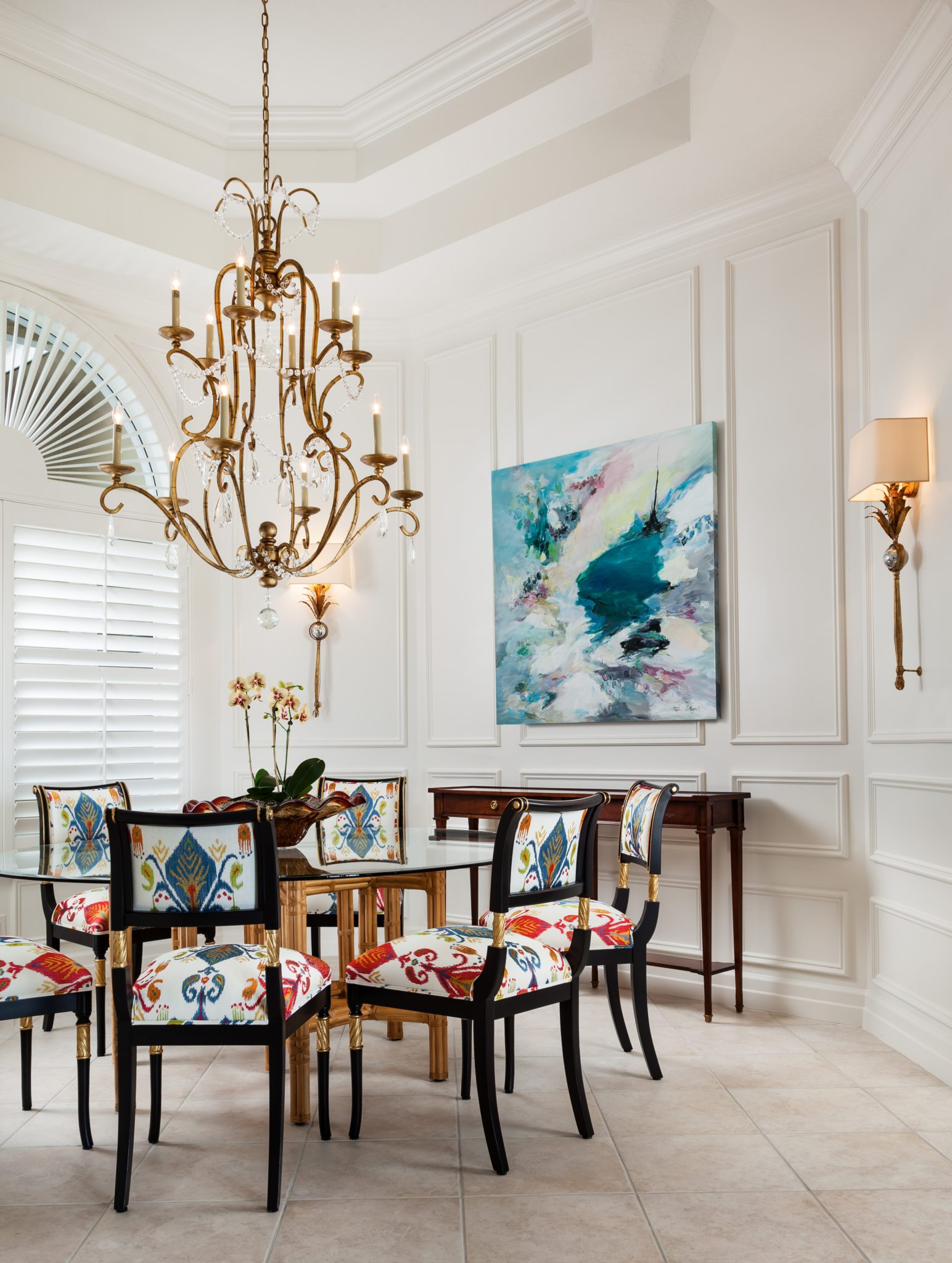 Dining chairs upholstered in patterned fabric, round glass top dining table and bronze chandelier with crystal pendants. By Gil Walsh Interiors