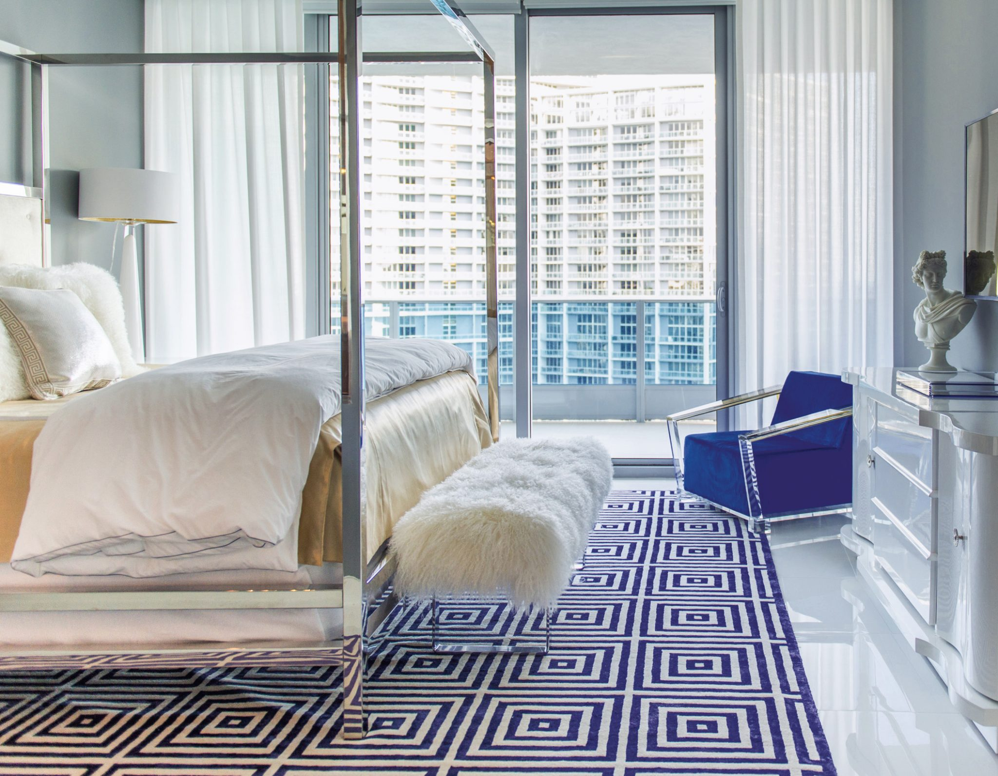 A master bedroom infused with sleek lines, shiny metal and pops of electric blues. By Taylor & Taylor