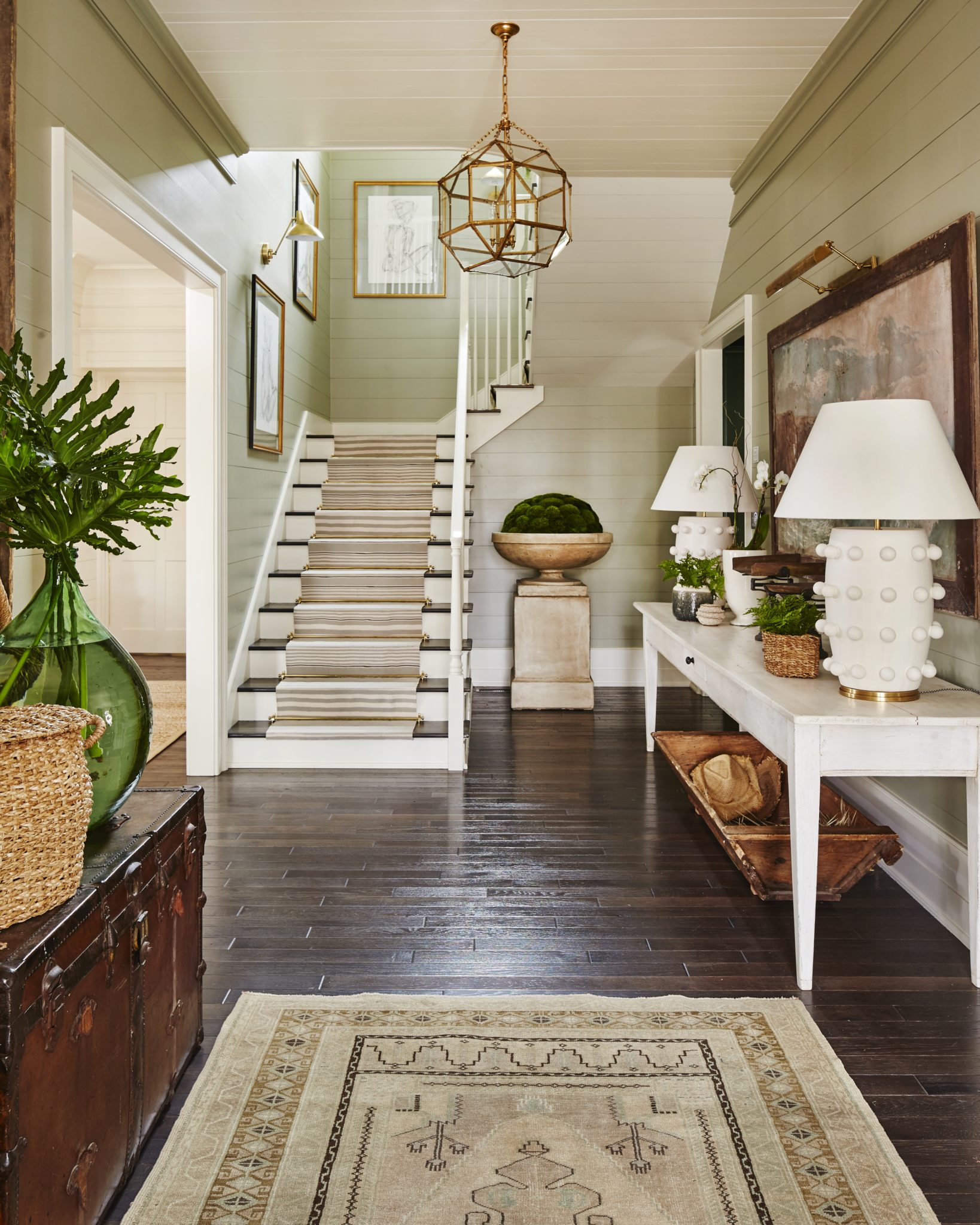 Southern Living foyer in painted shiplap, stair runner, vintage console & oushak by Ashley Gilbreath Interior Design