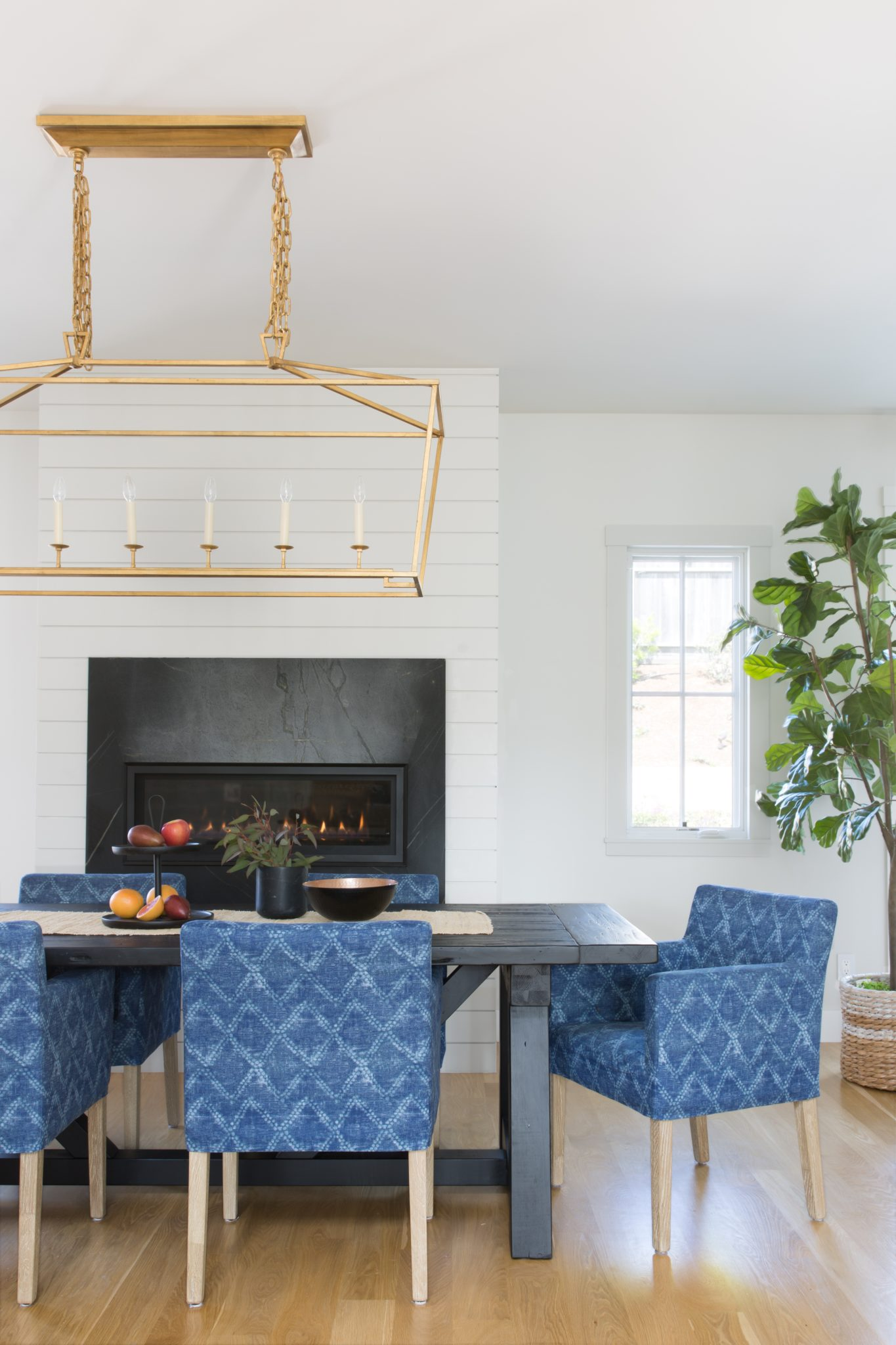 Dining room with shiplap, soapstone fireplace and blue boho dining chairs. by IDF Studio