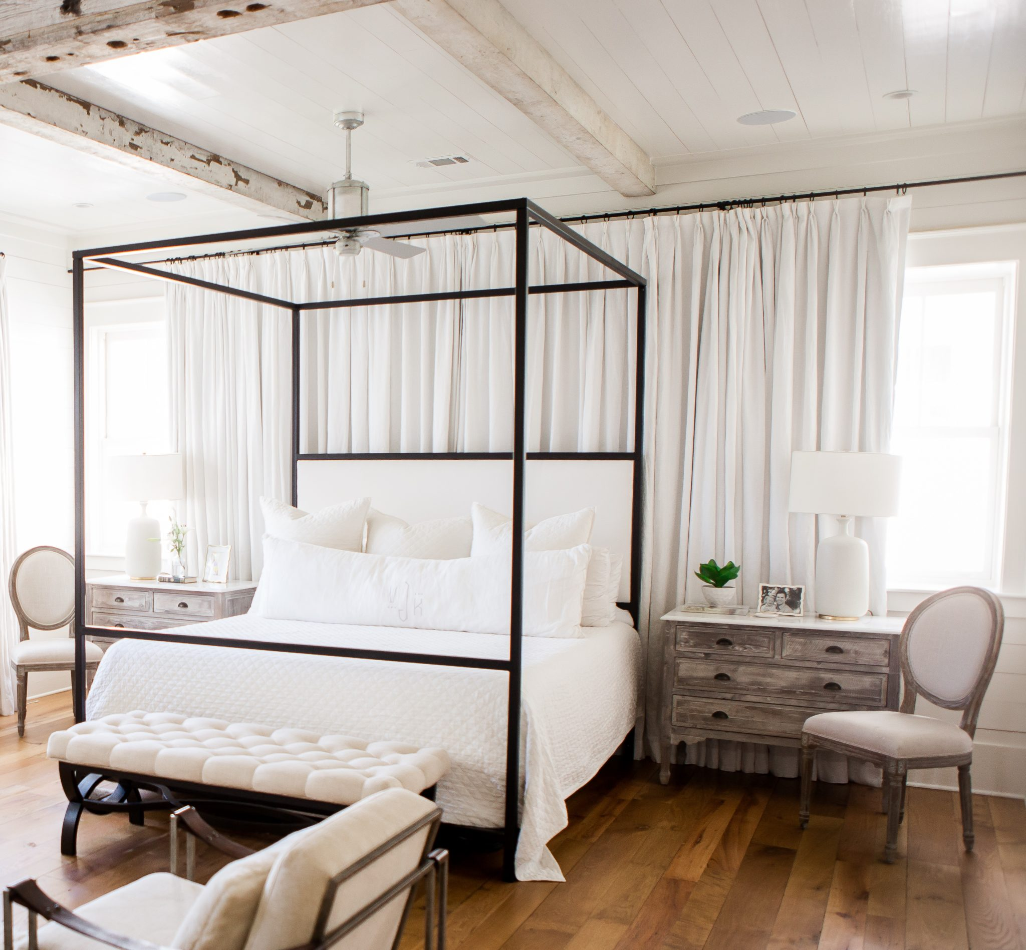 Master bedroom with ship lap walls, antique beam ceiling and white drapery. by Ashley Gilbreath Interior Design