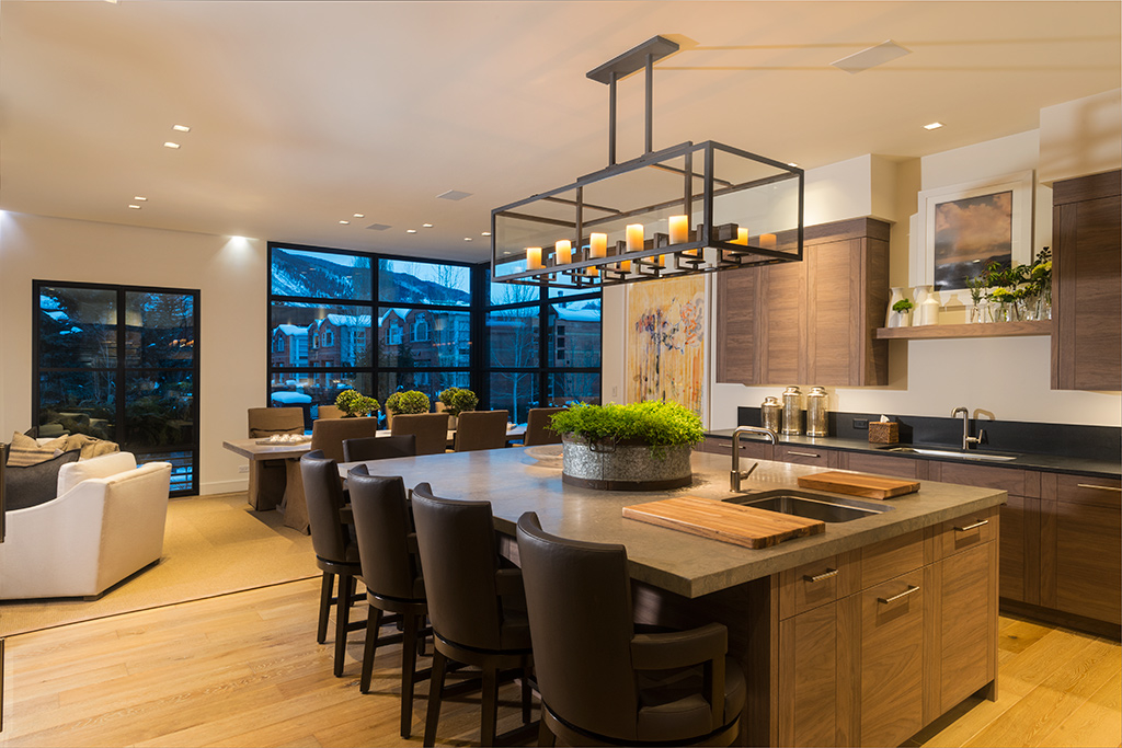 Weathered walnut cabinets, A. Rudin counter stools and contemporary art tie nicely to the adjacent kitchen in this modern Aspen home. By Kevin Corn Design