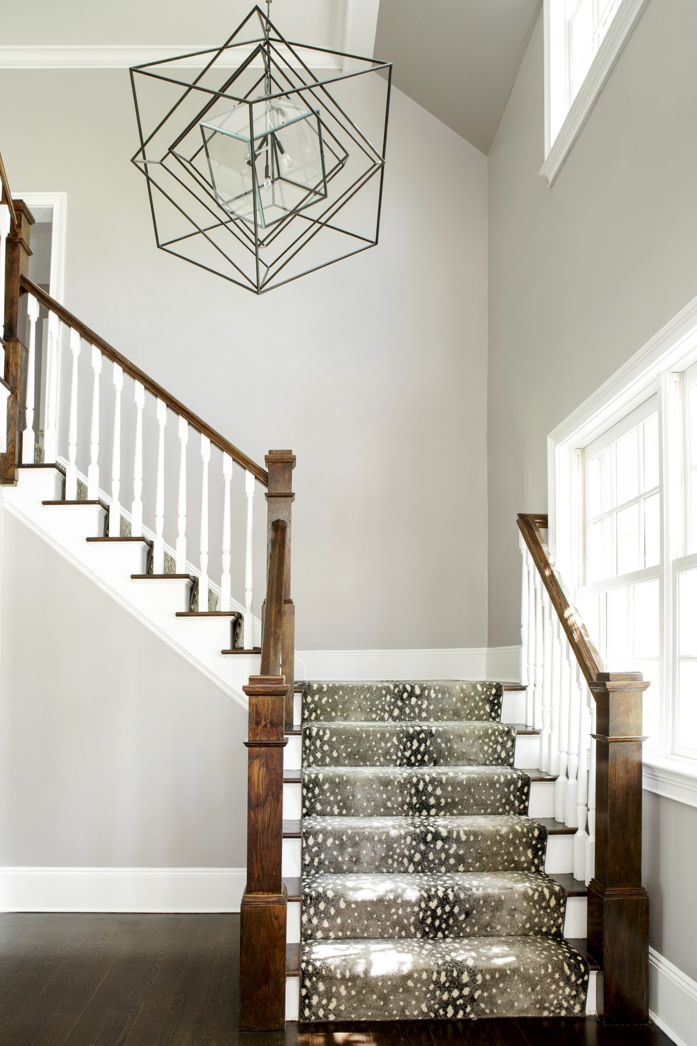 Bright foyer with animal print carpet on wraparound staircase statement light by Laura Michaels Design