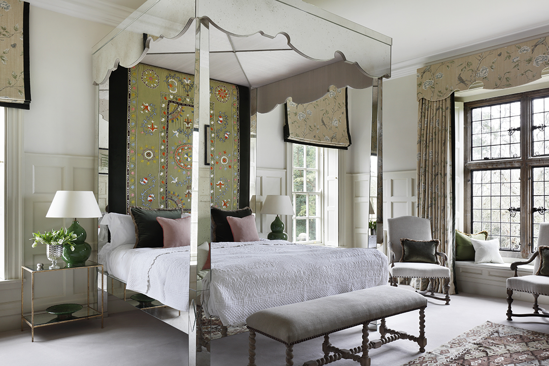 Elegant and boho bespoke bed with antique headboard in country house master suite by VSP Interiors