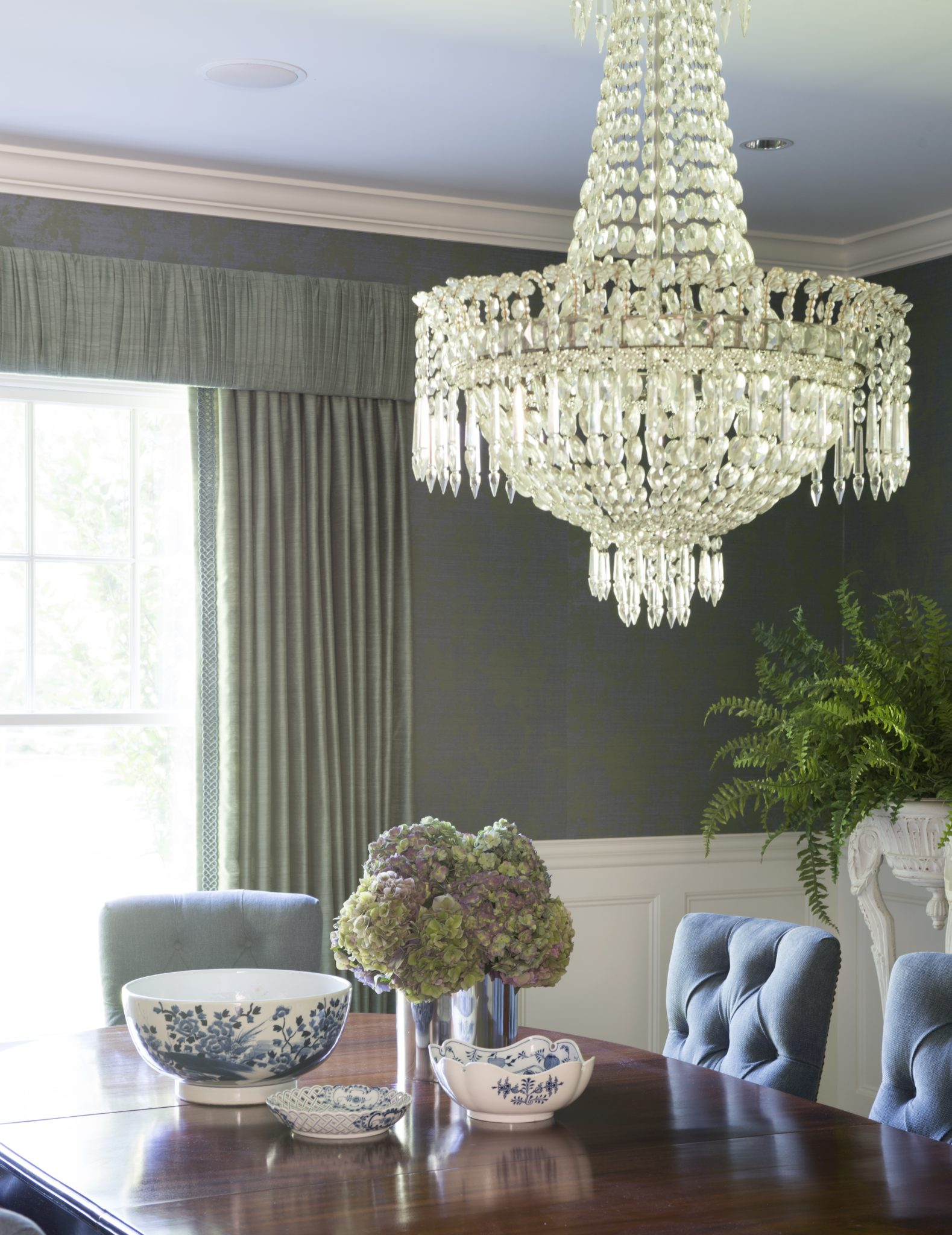 A statement chandelier in a dining room by Allison Caccoma, Inc.