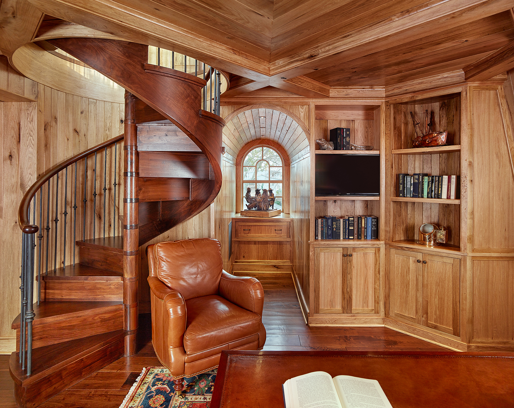 Butternut Wood Paneled Library with Wood Spiral Stair and Arched Window by Island Architects