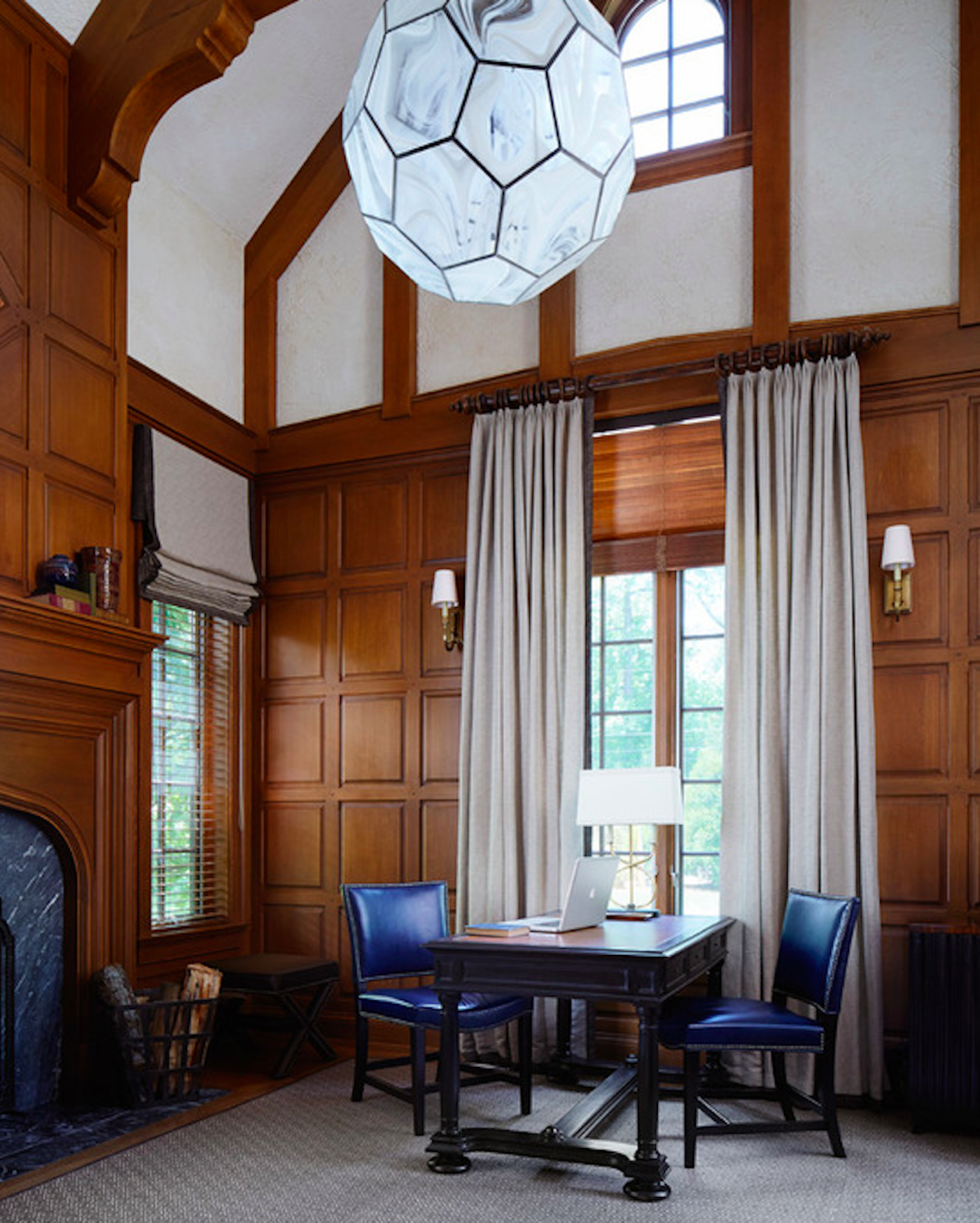 Imposing paneled walls are softened with simple curtains. by Schlagenhaft Studio