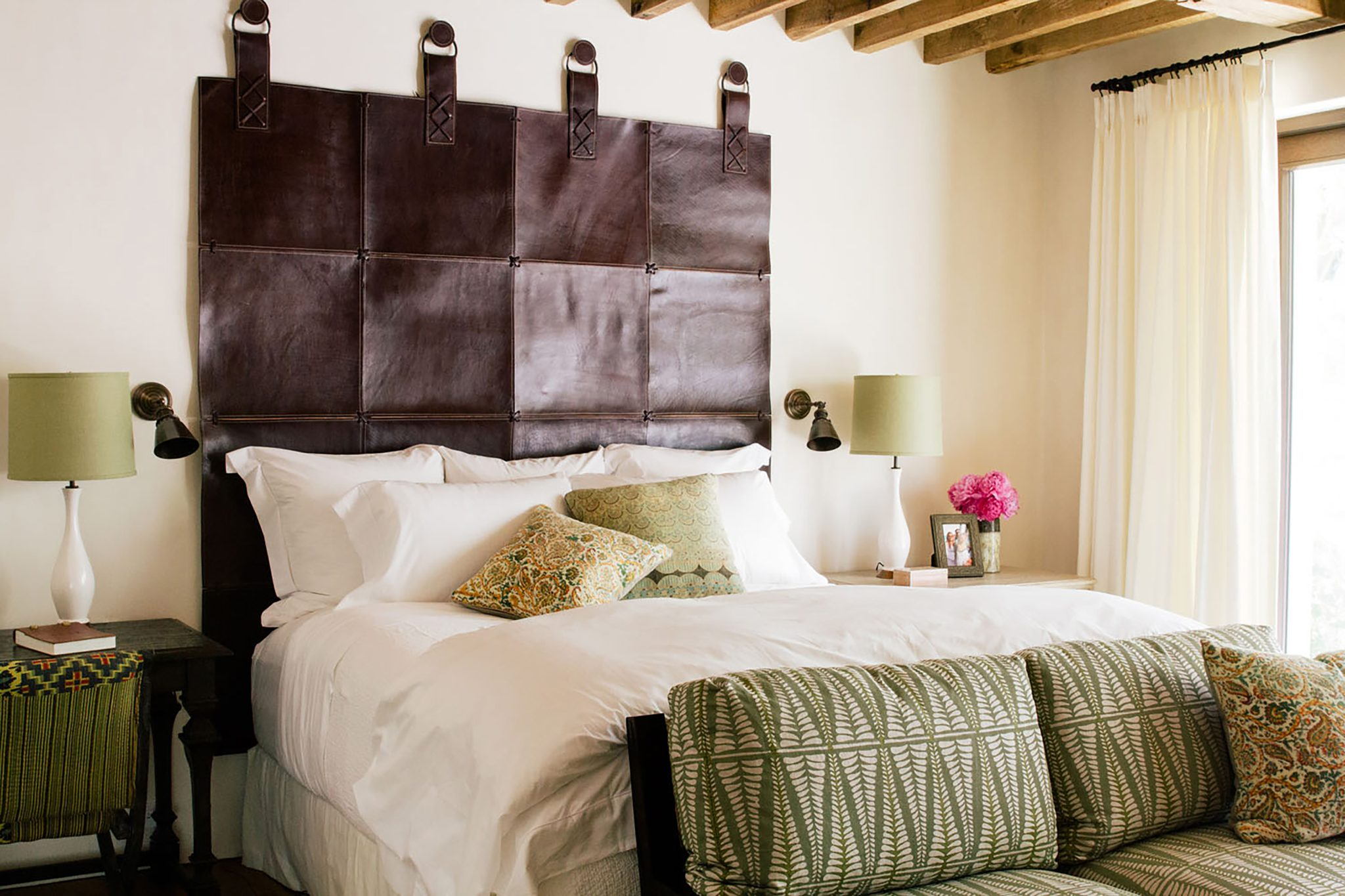 Leather headboard with giant nails, vintage beams by Chris Barrett Design