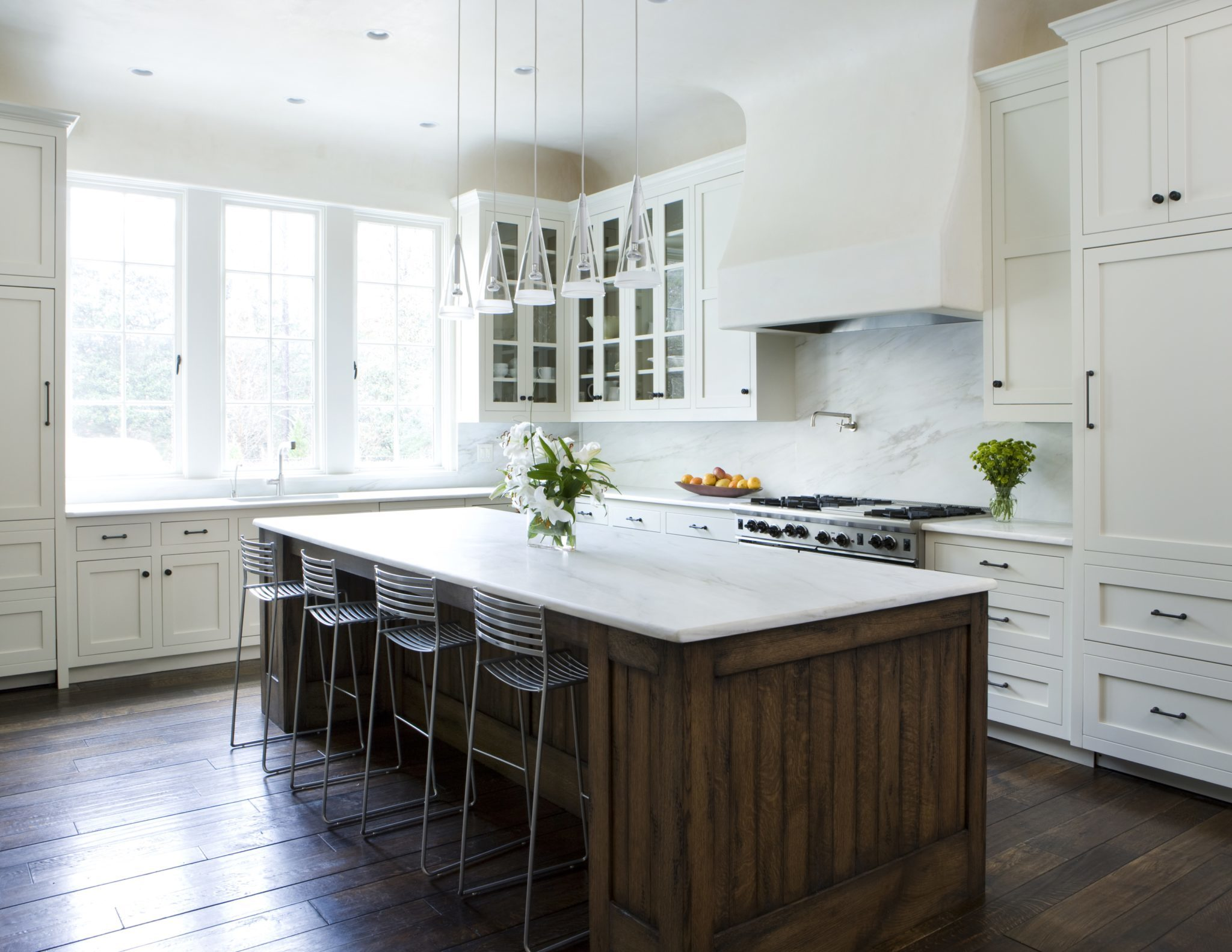 Large kitchen with wood floors and large island. By James Michael Howard