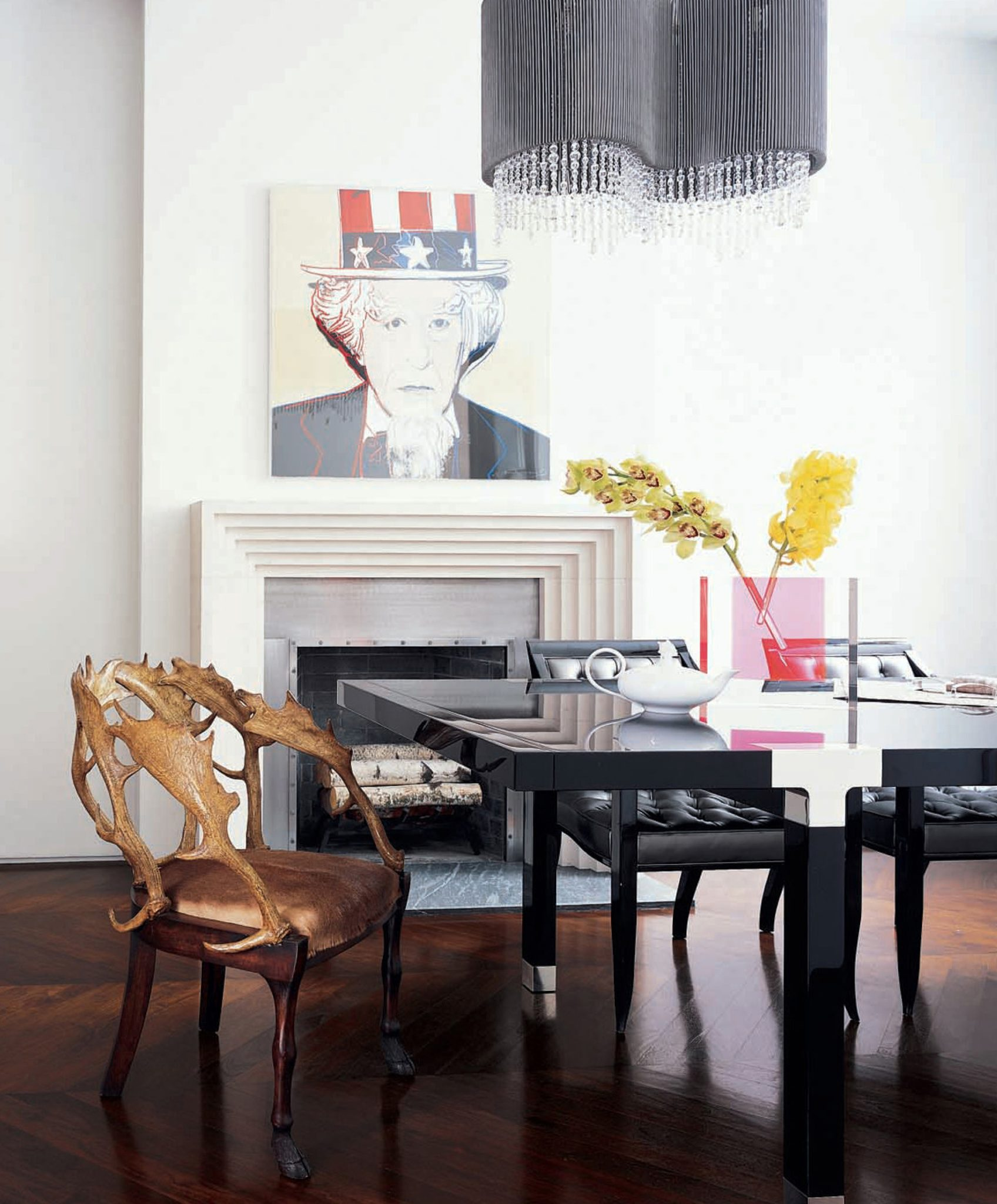 An Andy Warhol Uncle Sam overlooks the dining room, with its rustic faux-antler chair and lacquered Rossini table (from Armani/Casa); the chandelier is by Dominique Perrault from Sawaya & Moroni. by Axis Mundi