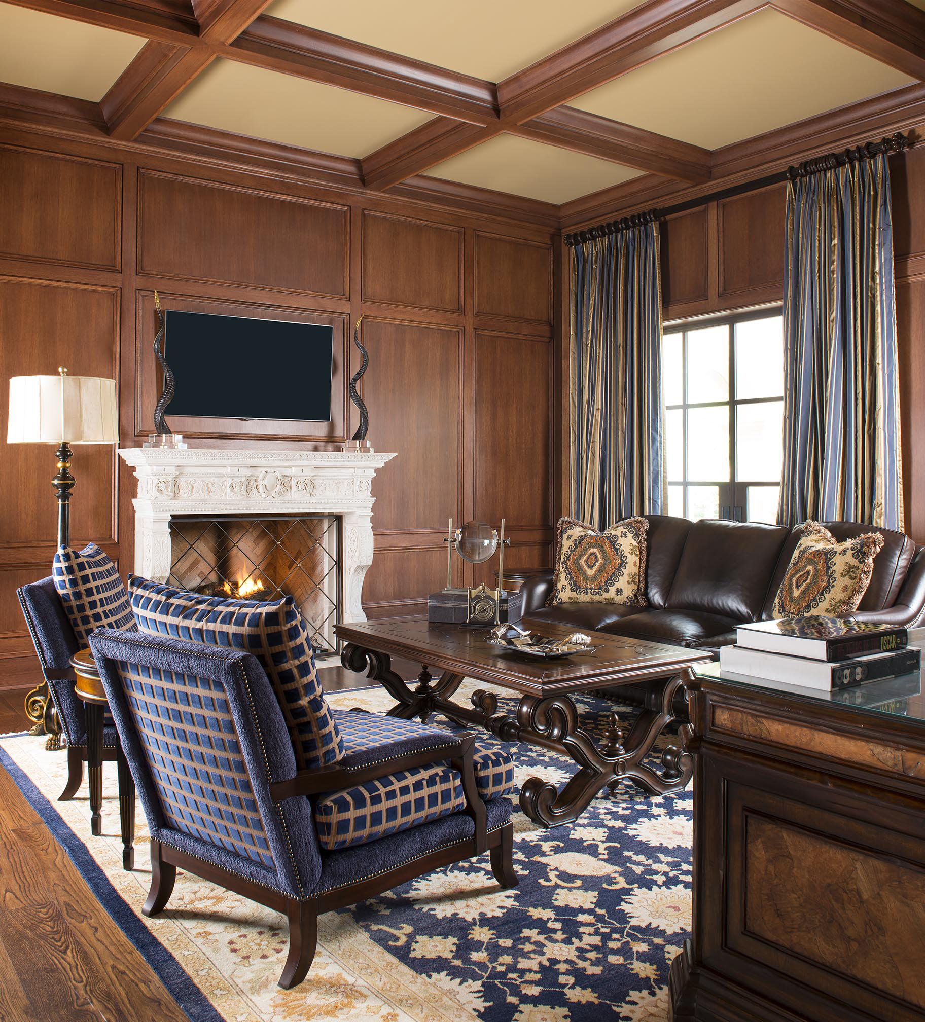 An elegant study with wood panels and a coffered ceiling. by Wesley-Wayne Interiors