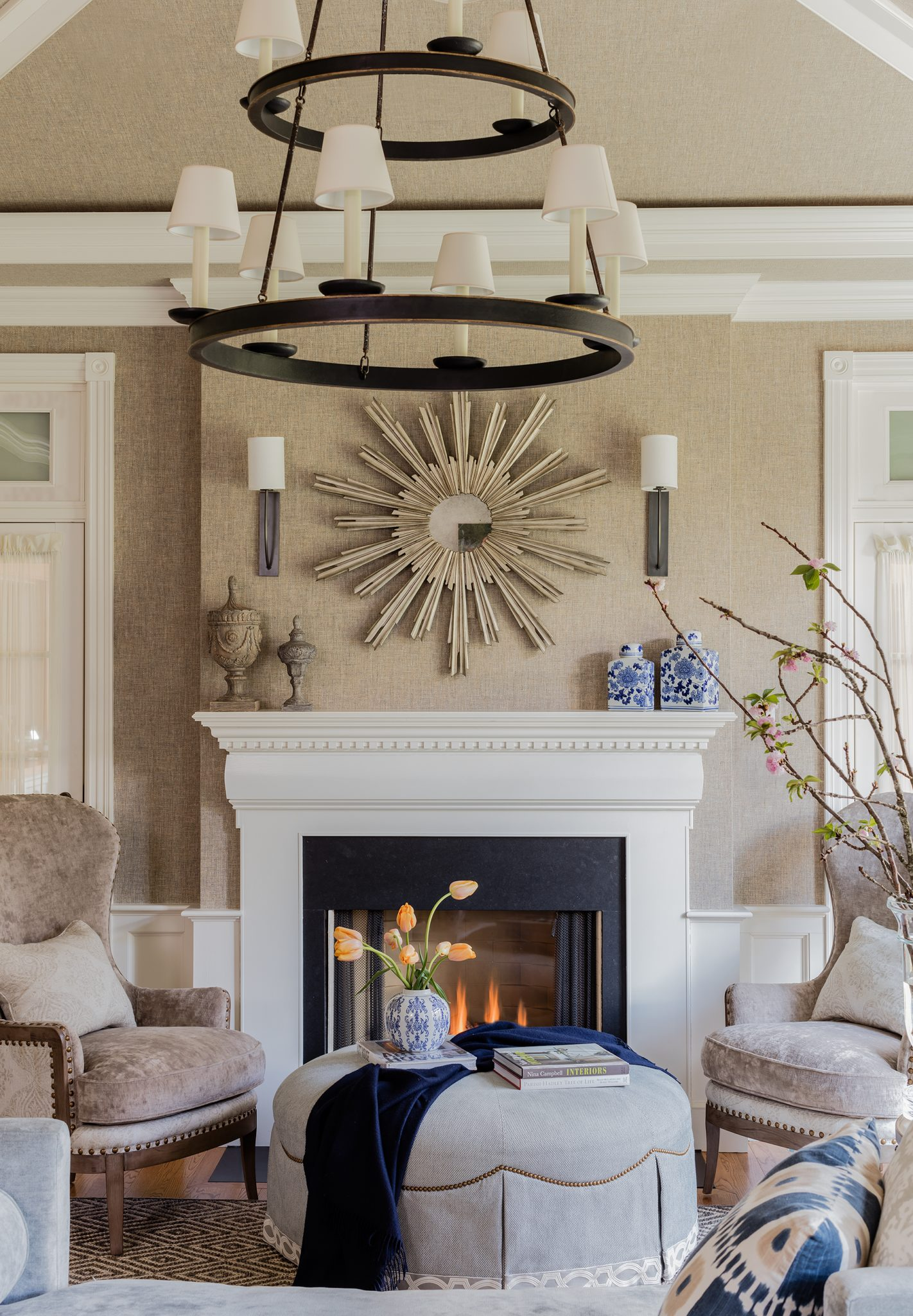Neutral beige living room with sunburst mirror, round ottoman and two-tier chandelier by Robin Gannon Interiors