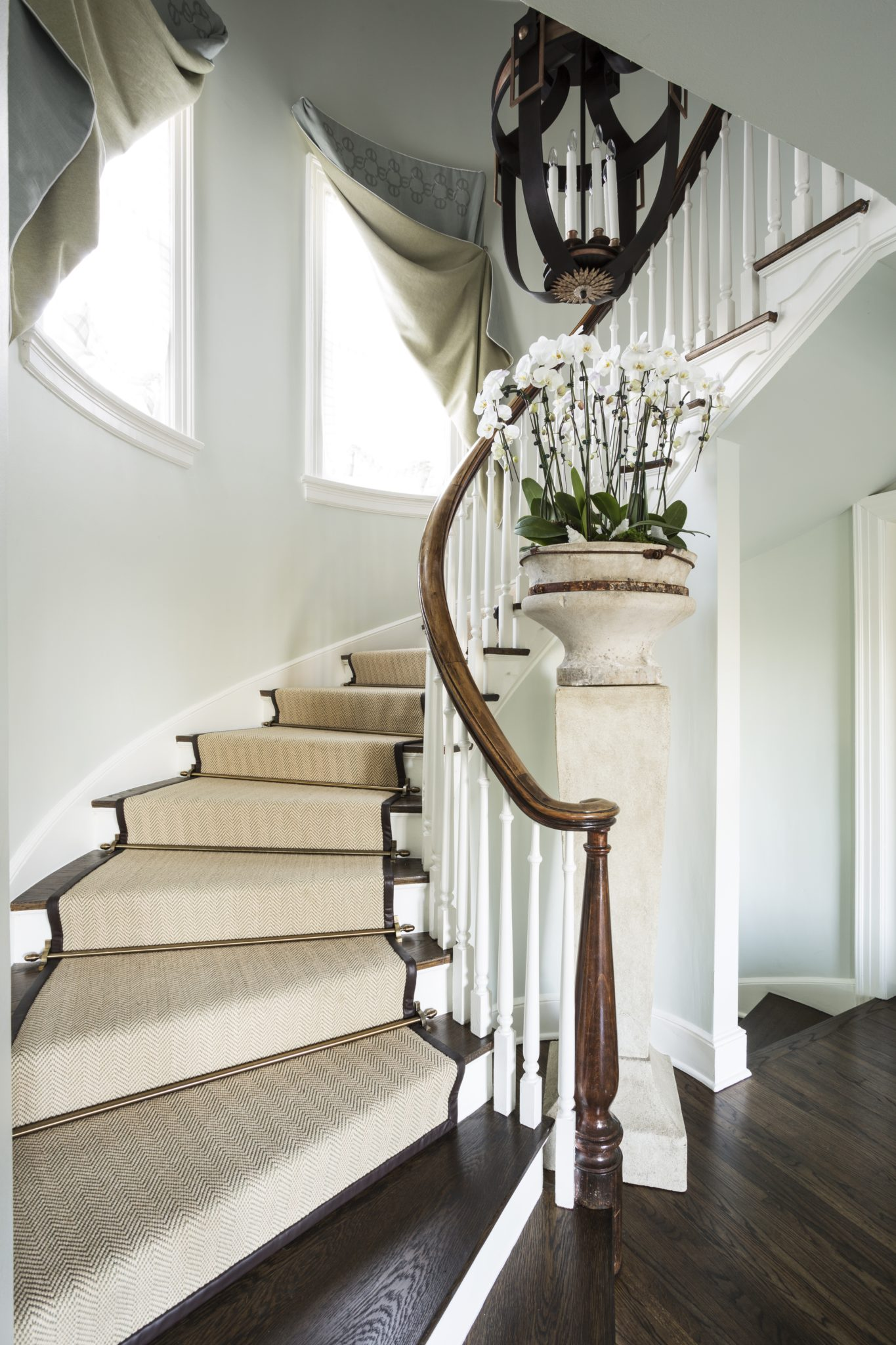 Grand staircase with leather bound sisal runner and architectural fragments by Goddard Design Group