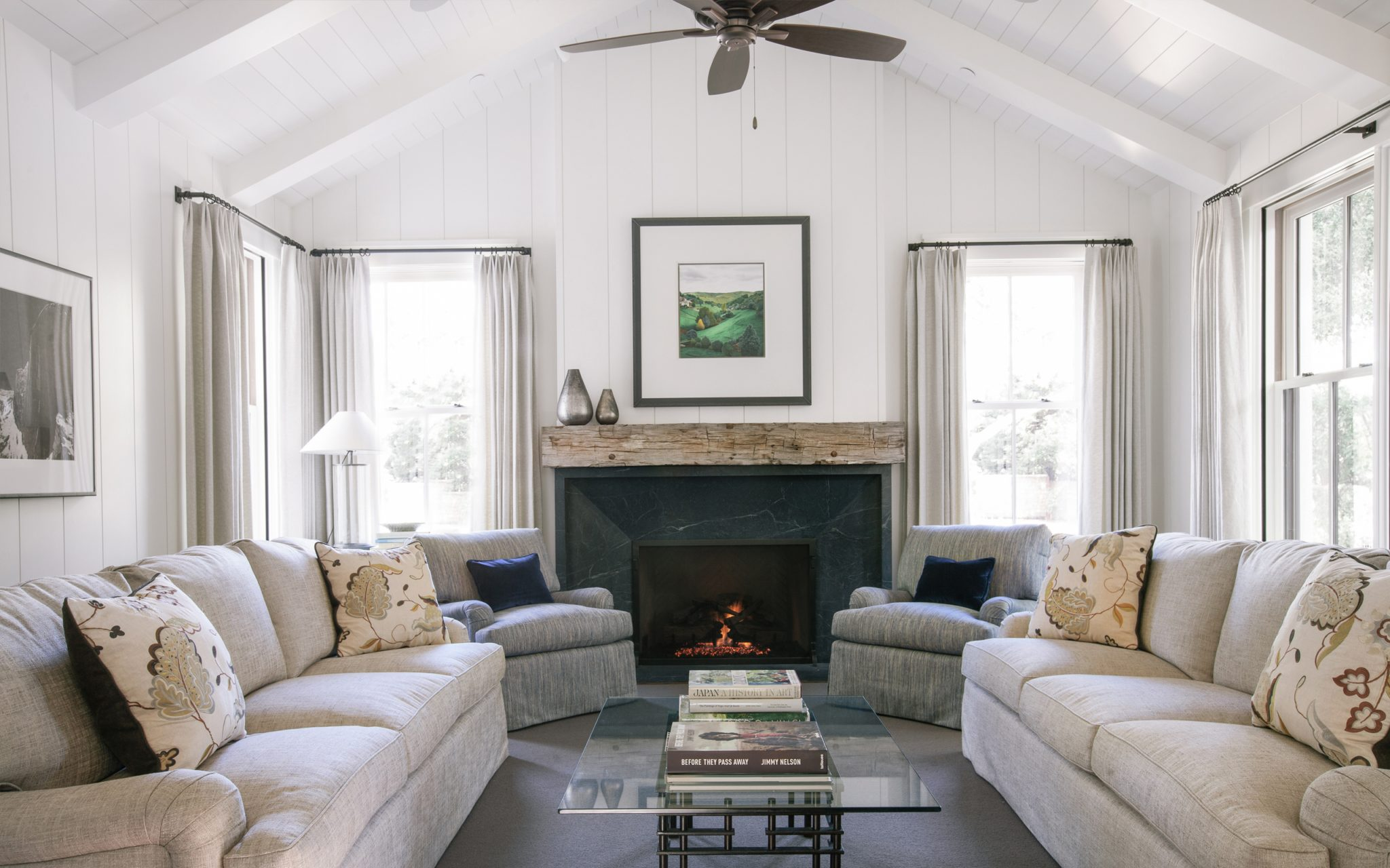 Contemporary farmhouse living room with plush seating, rustic wood mantle, fan by Fergus Garber Young Architects