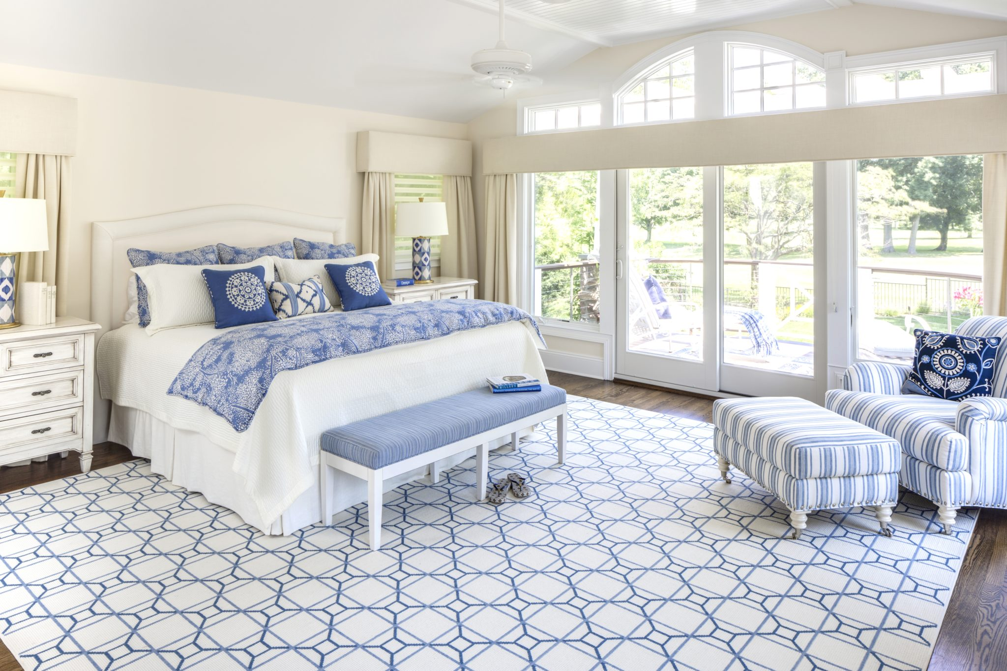 Master bedroom with a wall of windows and cool blues by Kim Radovich, Kim E. Courtney Interiors