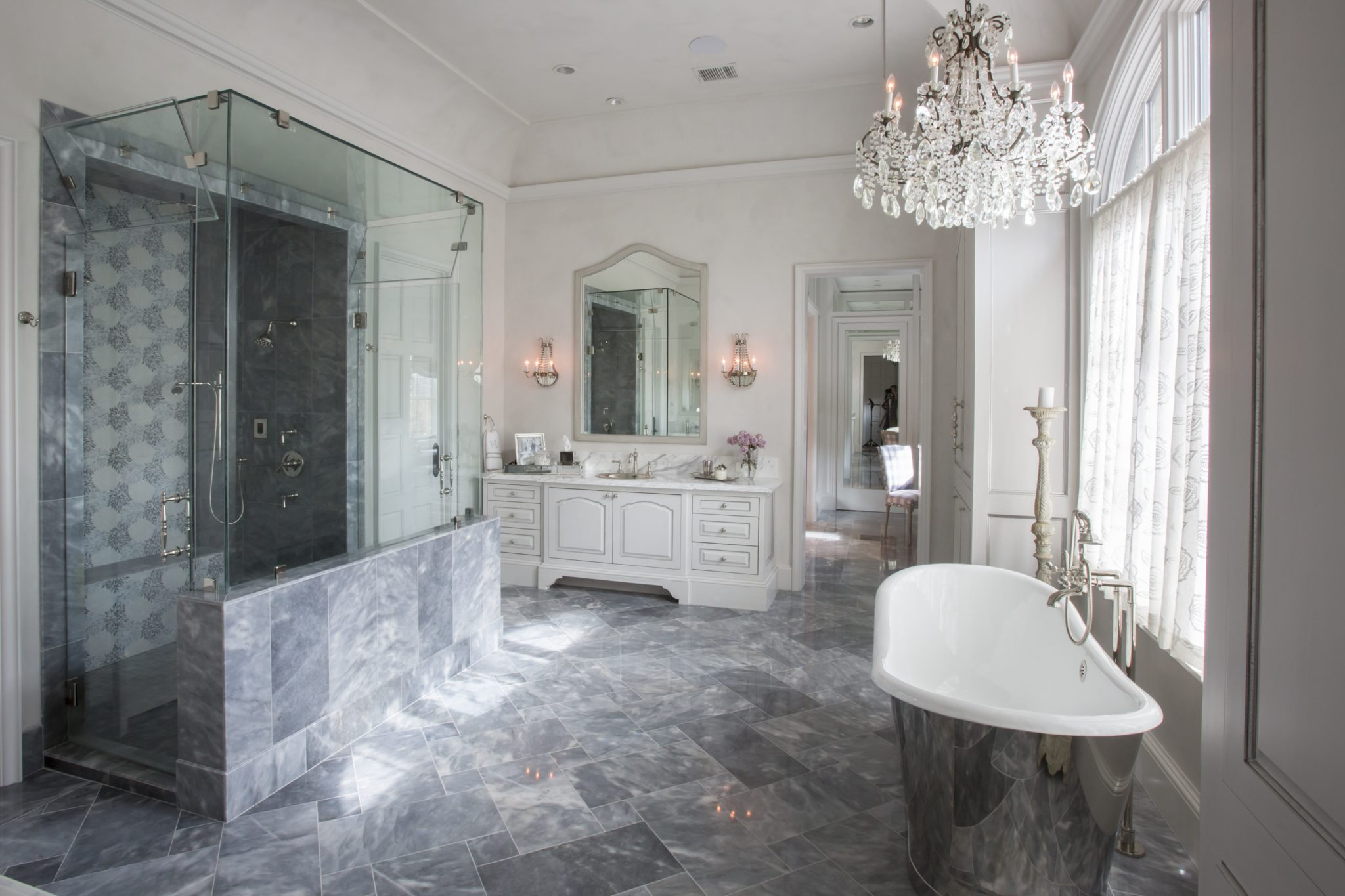 Luxurious master bath with a free standing tub & custom tile work by Triangle Interiors