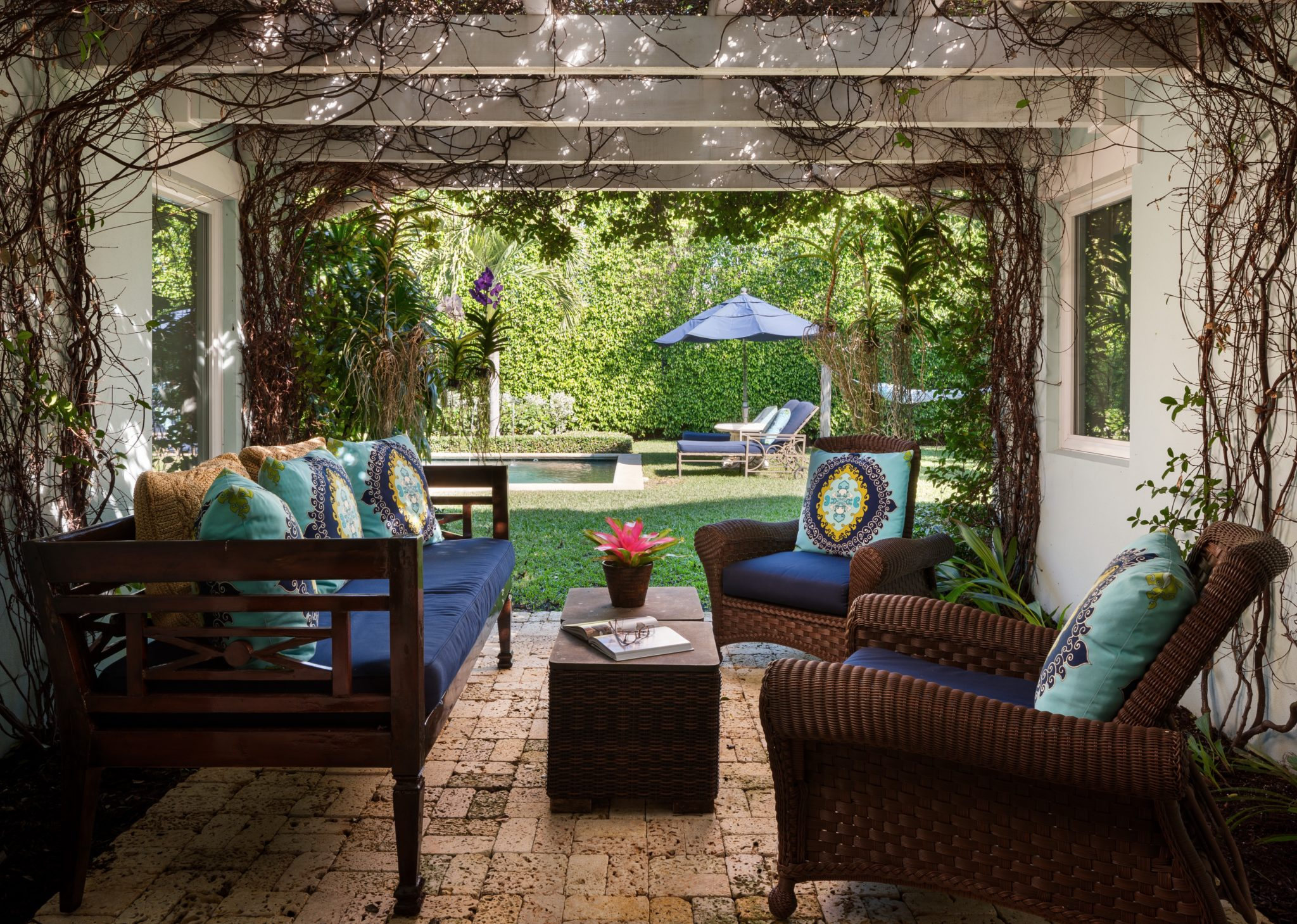 Outdoor pergola sitting area with coquina bricks and custom cushions by Margaret Costello Interiors
