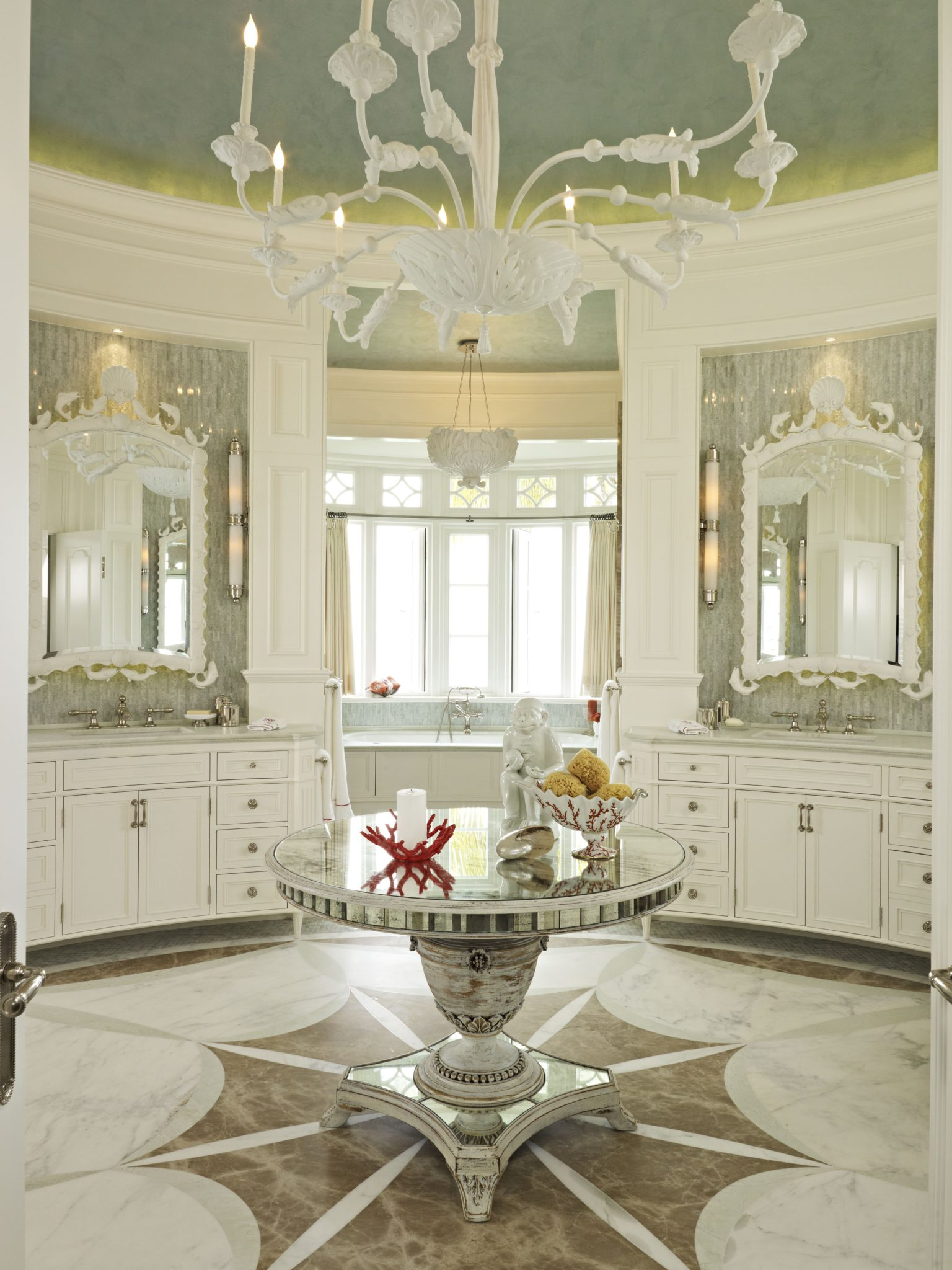 Reflective surfaces define this bathroom. The mirrors over the sinks have shell and fish motifs. A neoclassical starburst pattern in three colors of marble reinforces the room's geometry. By Taylor & Taylor