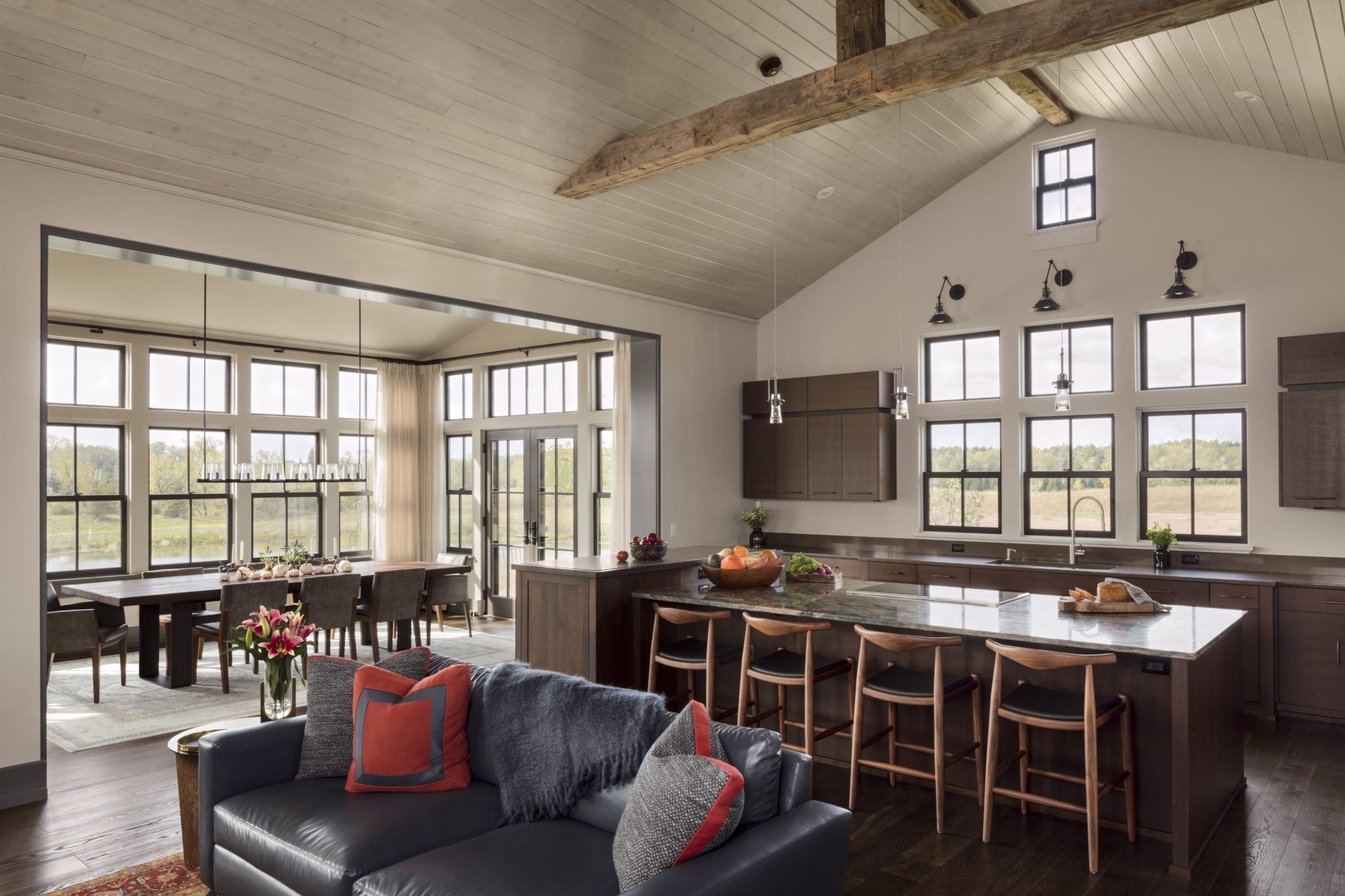 An open kitchen with soaring ceilings, rustic wood beams & natural light. by Wade Weissmann Architecture Inc.