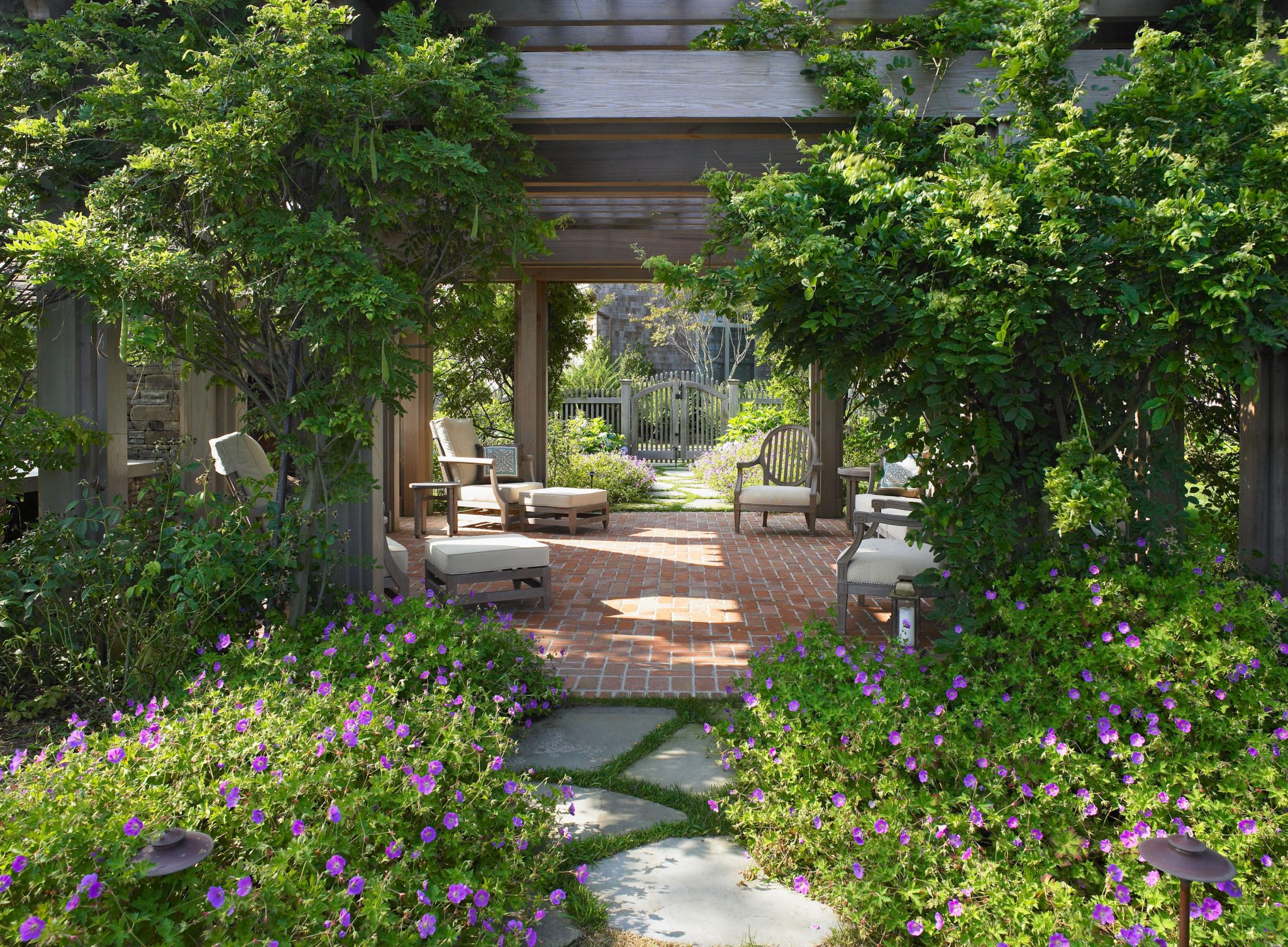Vine covered pergola with natural-stone path bordered by blue flowered geranium by Hollander Design Landscape Architects