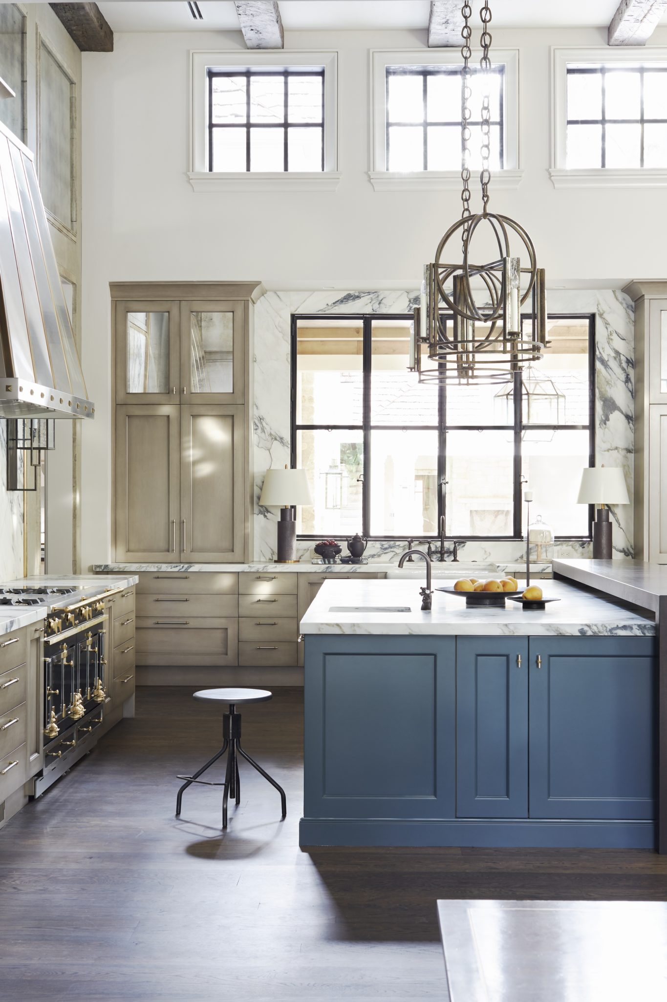High-ceilinged kitchen with blue island cabinets, exposed beams by Matthew Quinn