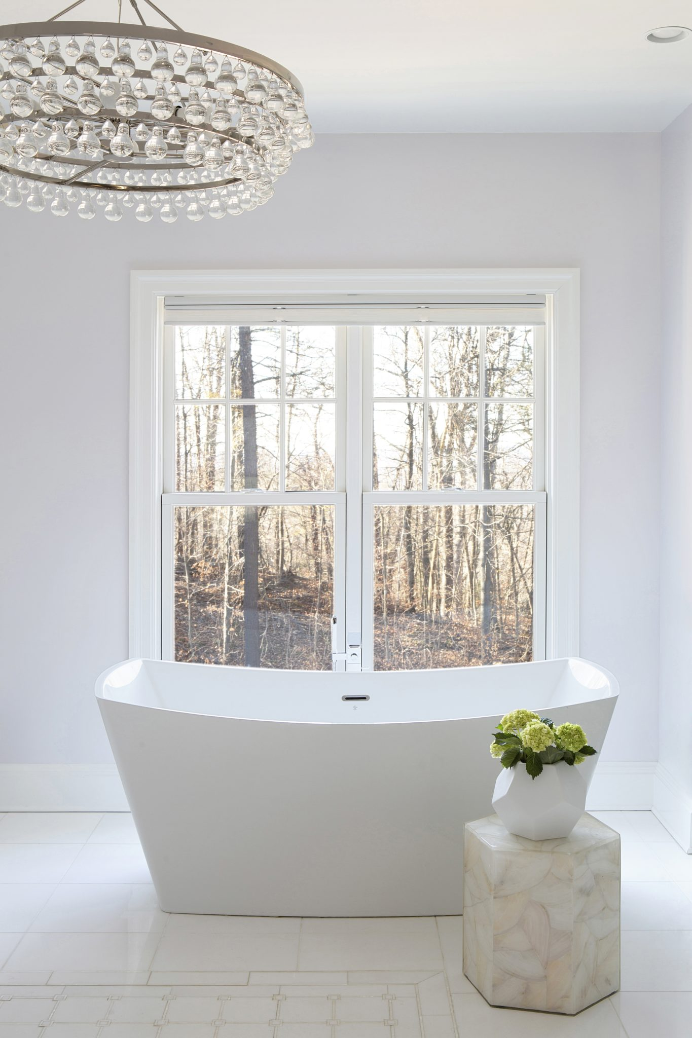 All white bathroom with majestic soaker tub. by Laura Michaels Design