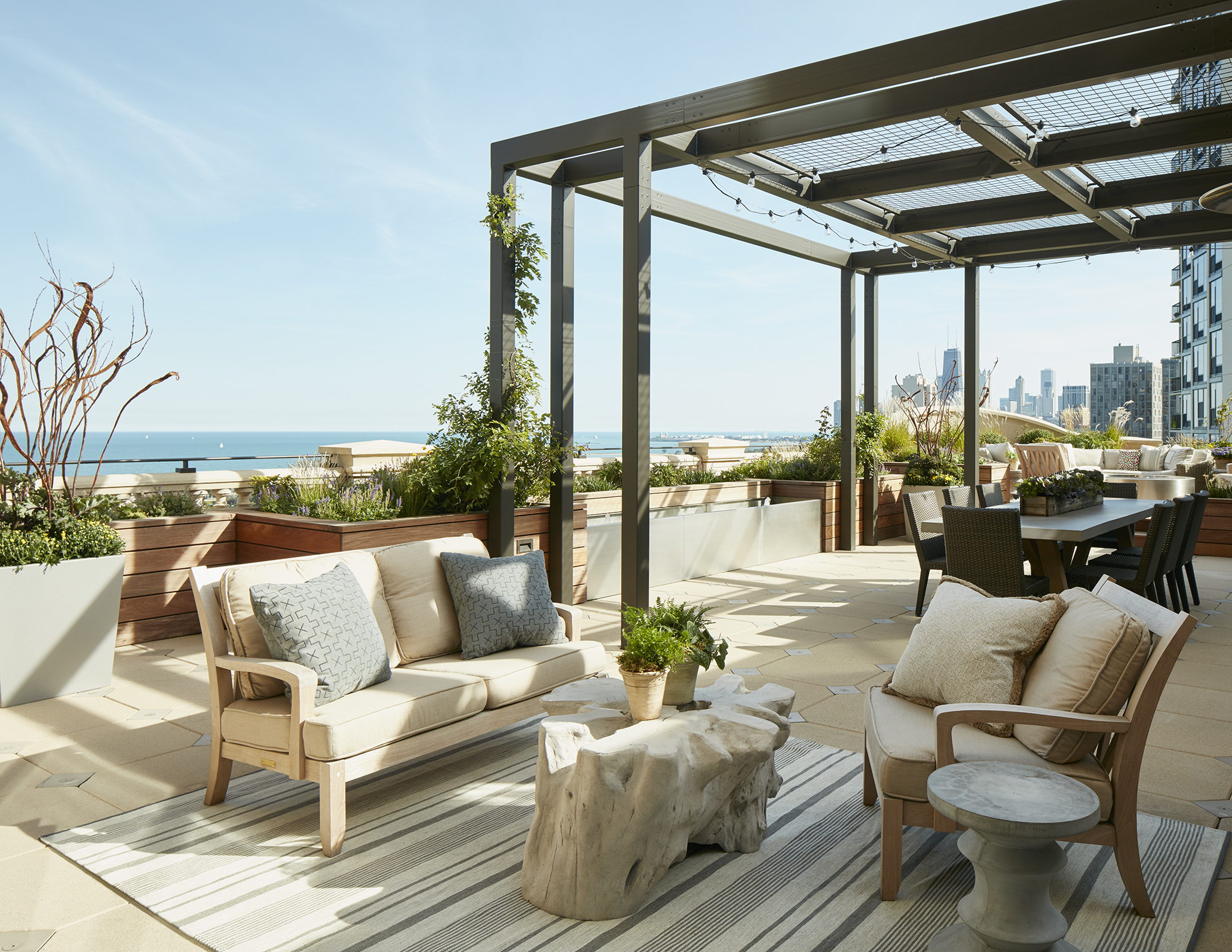 Chicago Penthouse: Elegant Rooftop Terrace with Seating Area and Metal Pergola by bba ARCHITECTS