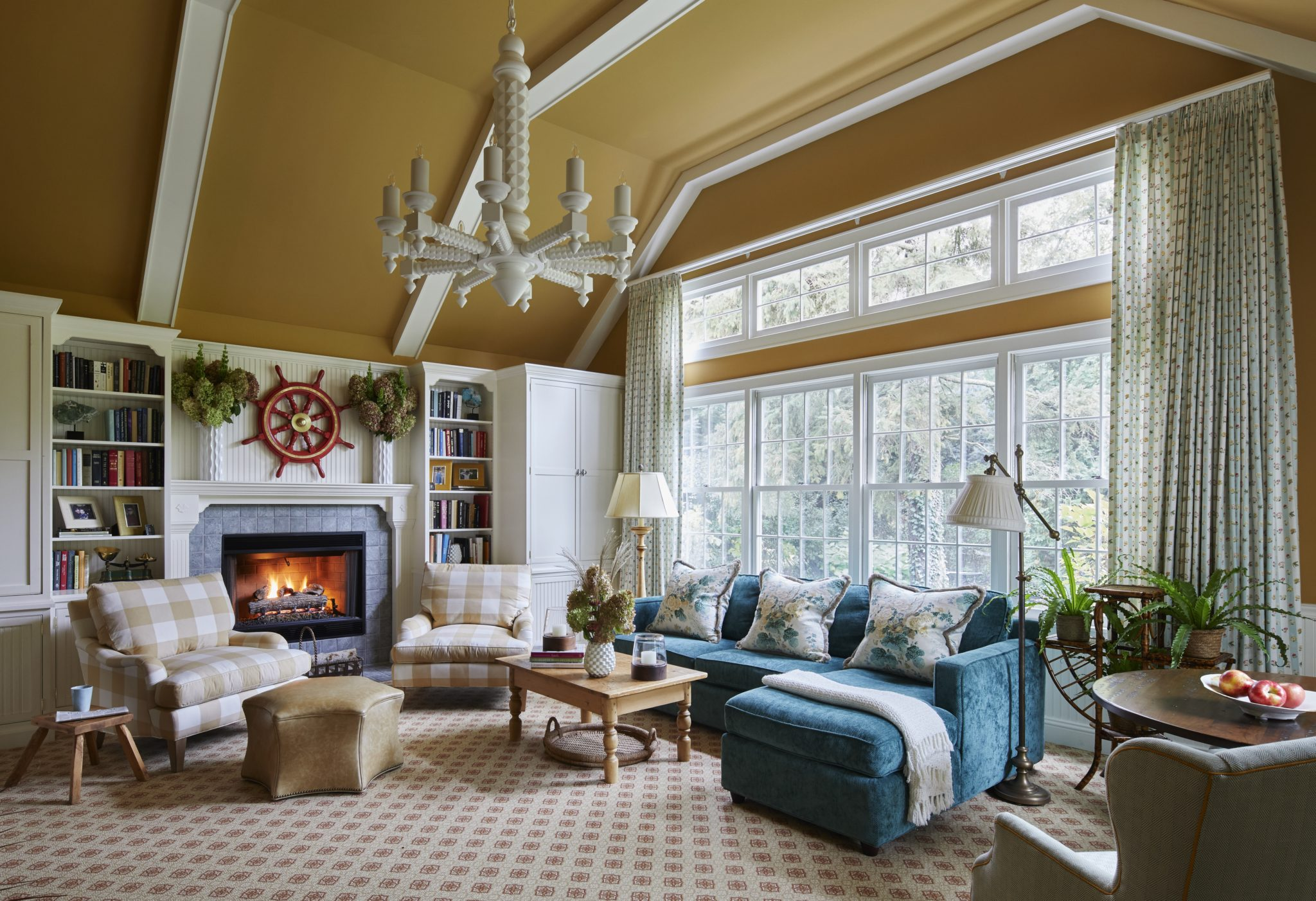 Teal, tan, red with white fireplace cabinetry, beamed ceiling, large chandelier by Elizabeth Drake