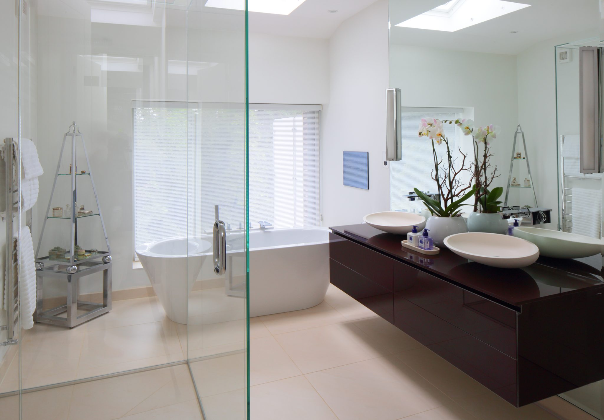 A contemporary master bathroom with a freestanding bath and shower by dk INTERIORS