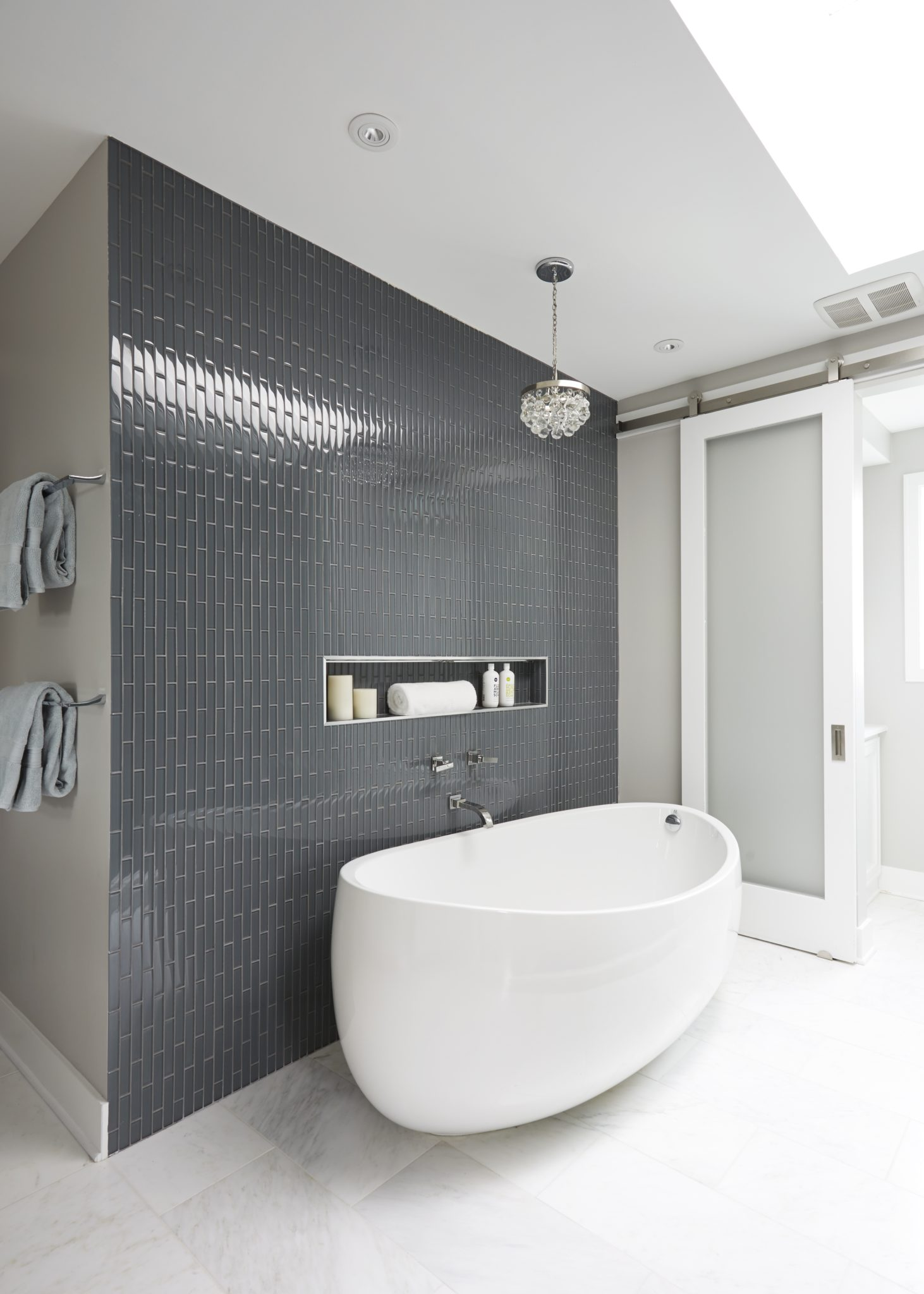 Modern condo master bathroom with blue vertical wall tile, skylight, and a glass pendant by Maren Baker Design