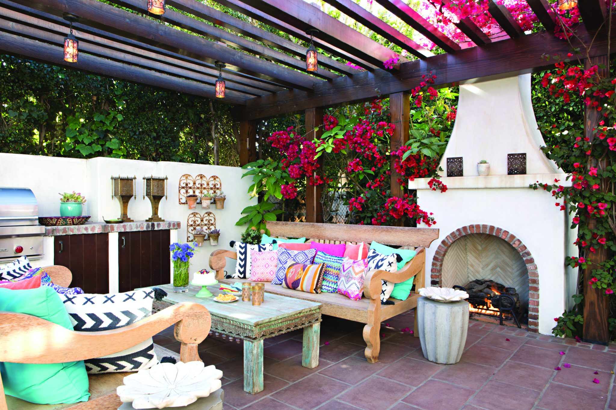 Pergola with outdoor kitchen, fireplace, and lounge area by Tim Barber Ltd.