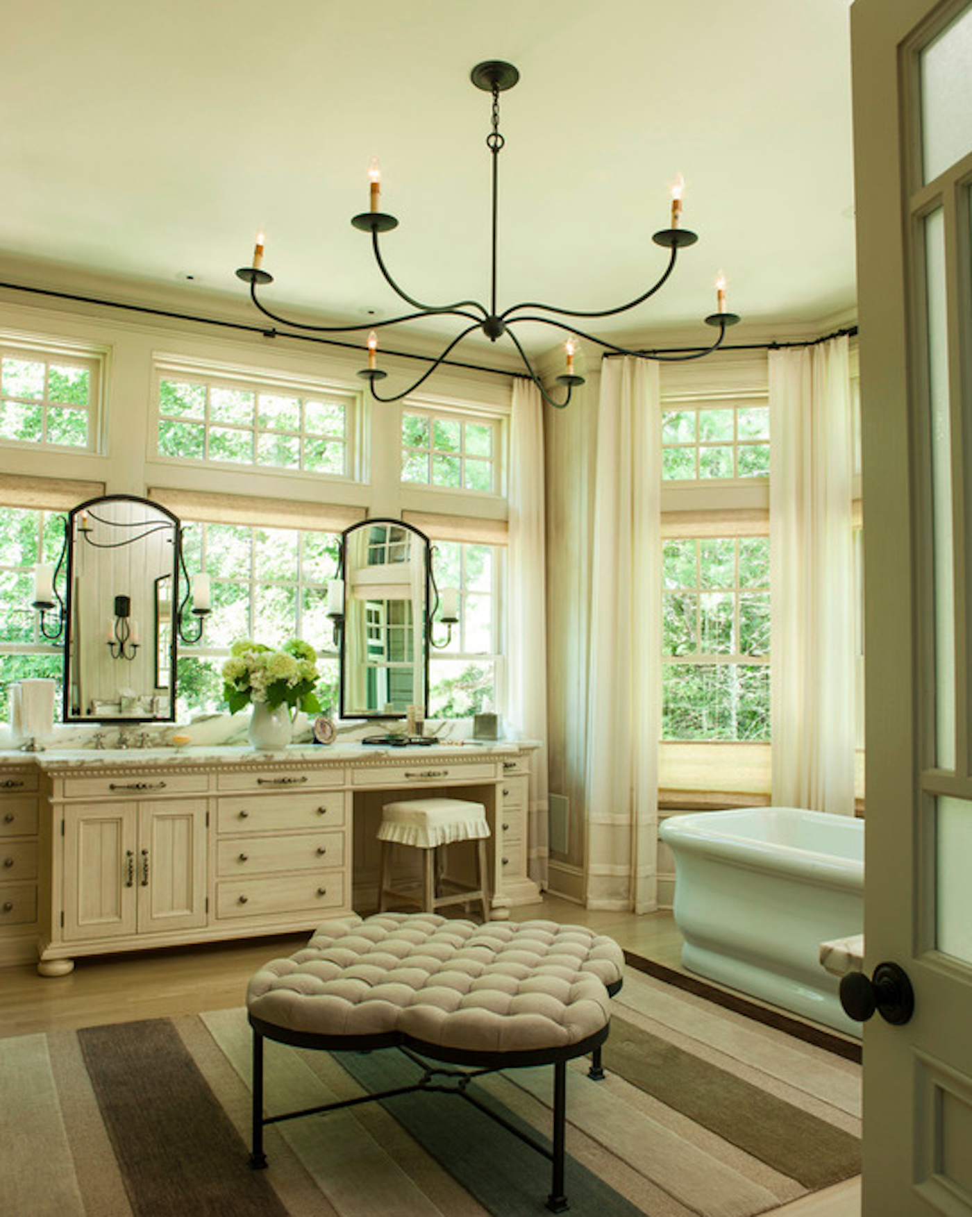 Bay windows brighten this classic master bathroom. by Taylor & Taylor