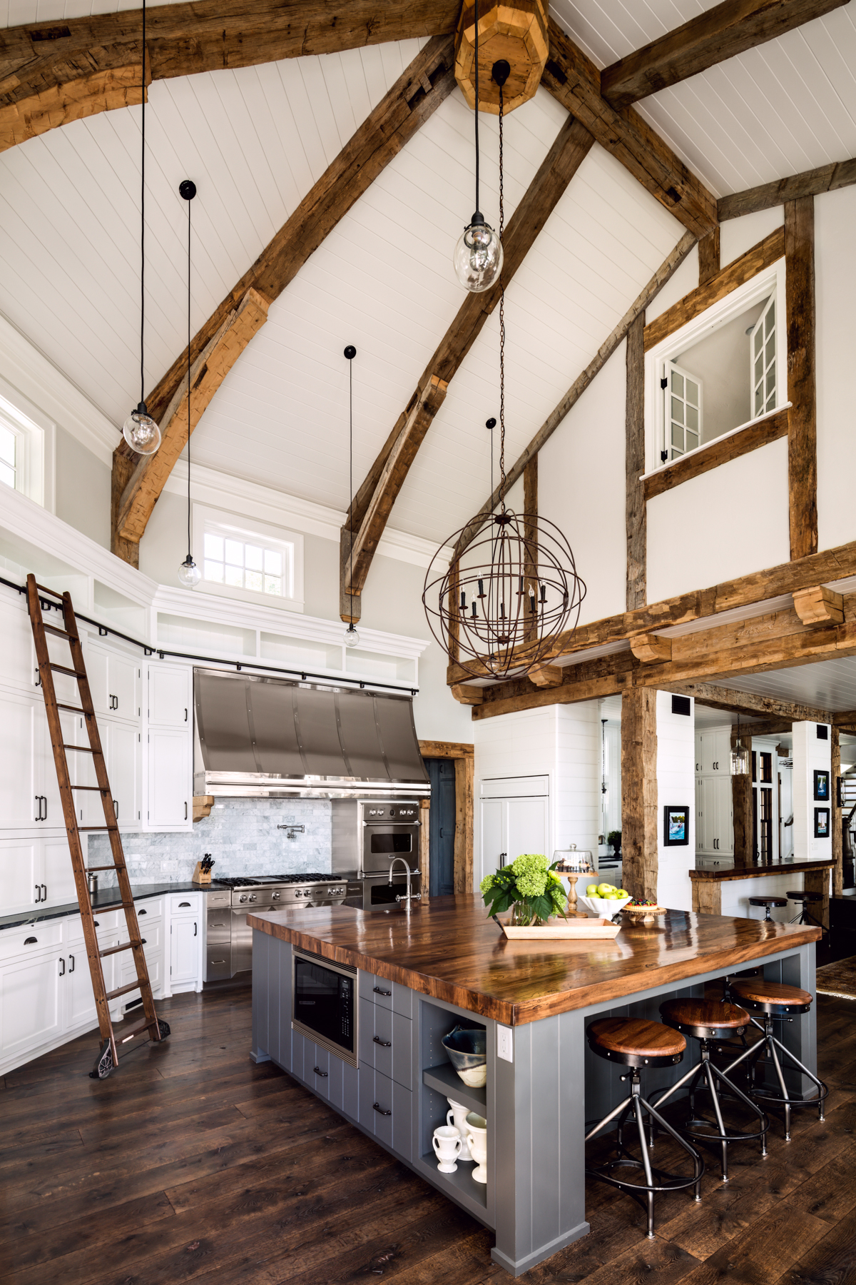 Double height, shaped kitchen ceiling with heavy timber beams by Wade Weissmann Architecture Inc.