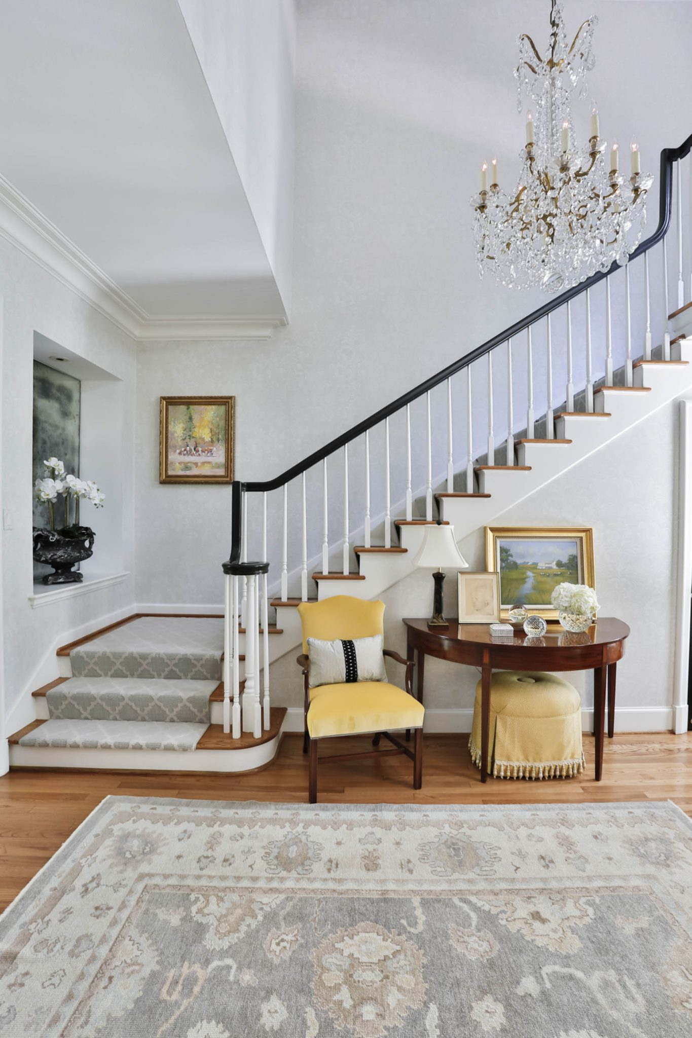 Traditional entry hall & stairway with a soft neutral & yellow palette by Triangle Interiors