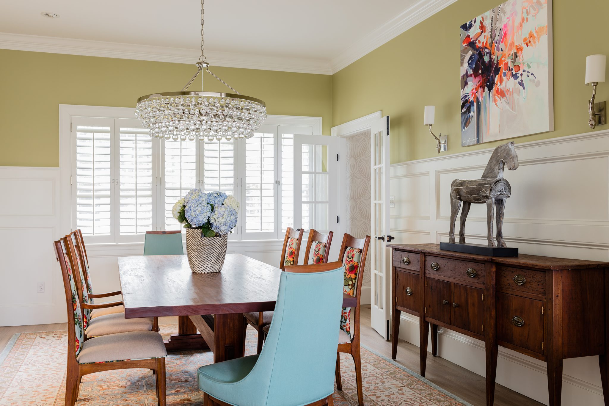 Bold color and high white paneling update a traditional dining room by Kathy Marshall Design