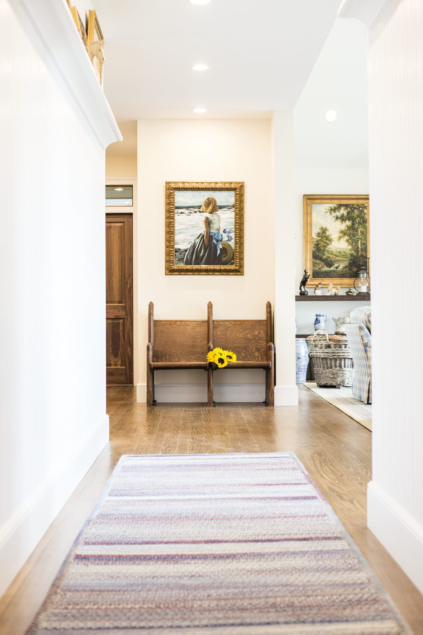 Farmhouse, Hallway Leading to Antique Church Pew and Bright Artwork by LSM Interior Design