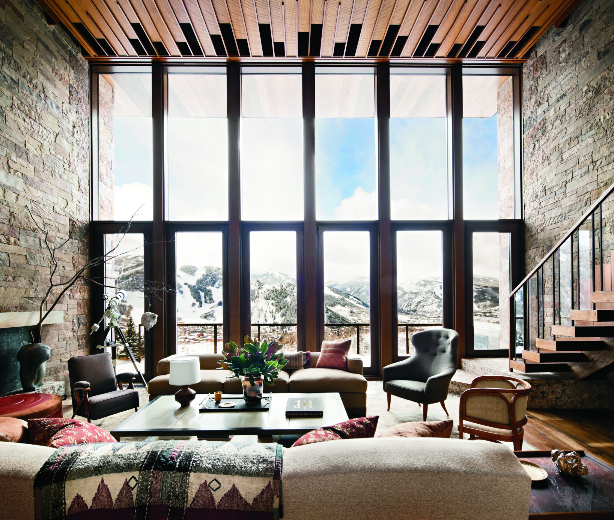 A double-height living room with sweeping views of Red Mountain in Aspen. By Studio Sofield