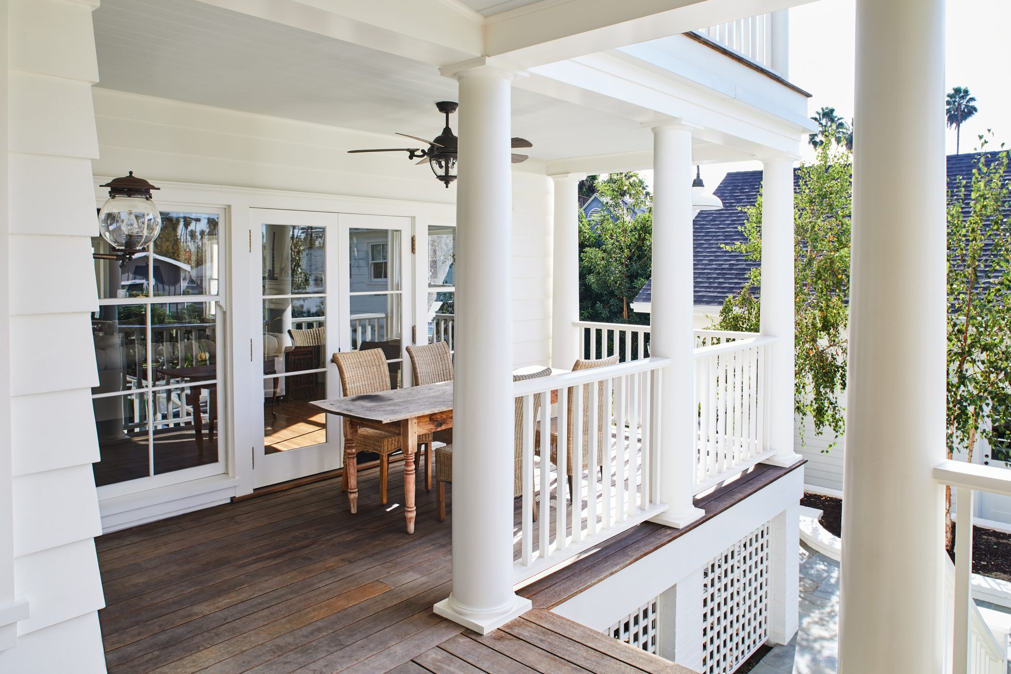 Covered back porch with columns of Southern Neoclassical style residence by Tim Barber Ltd.