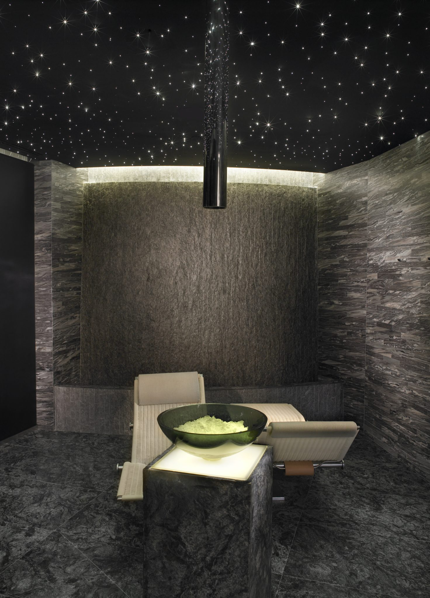 Neutral chaise lounges rest beneath a black star lit ceiling and slate walls. by Michael Wolk Design Associates