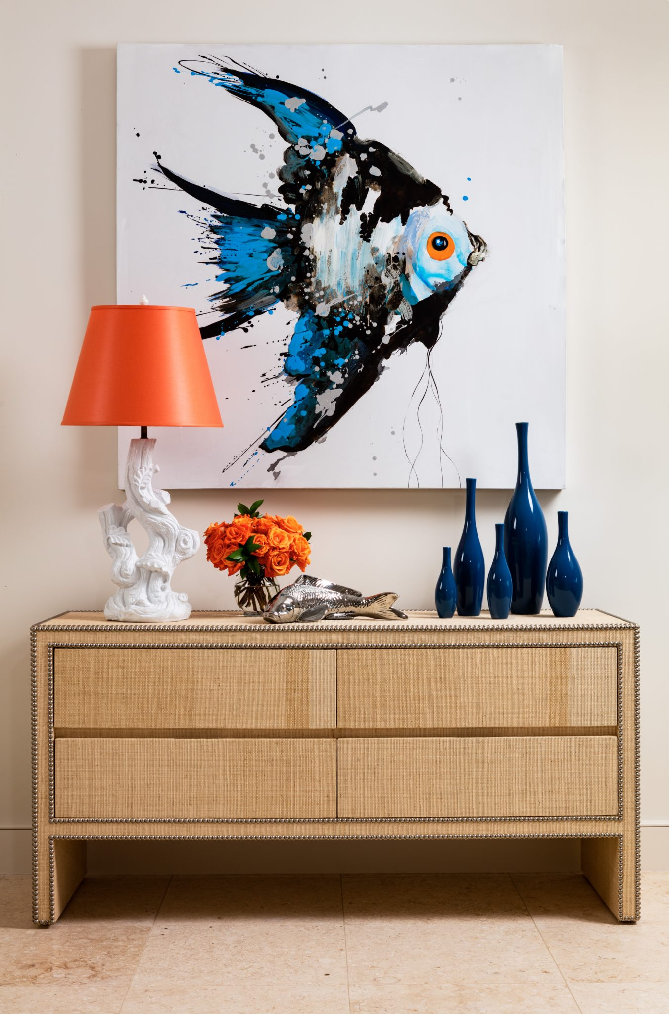 A large painting of a single tropical fish tops a raffia credenza. by Gil Walsh Interiors