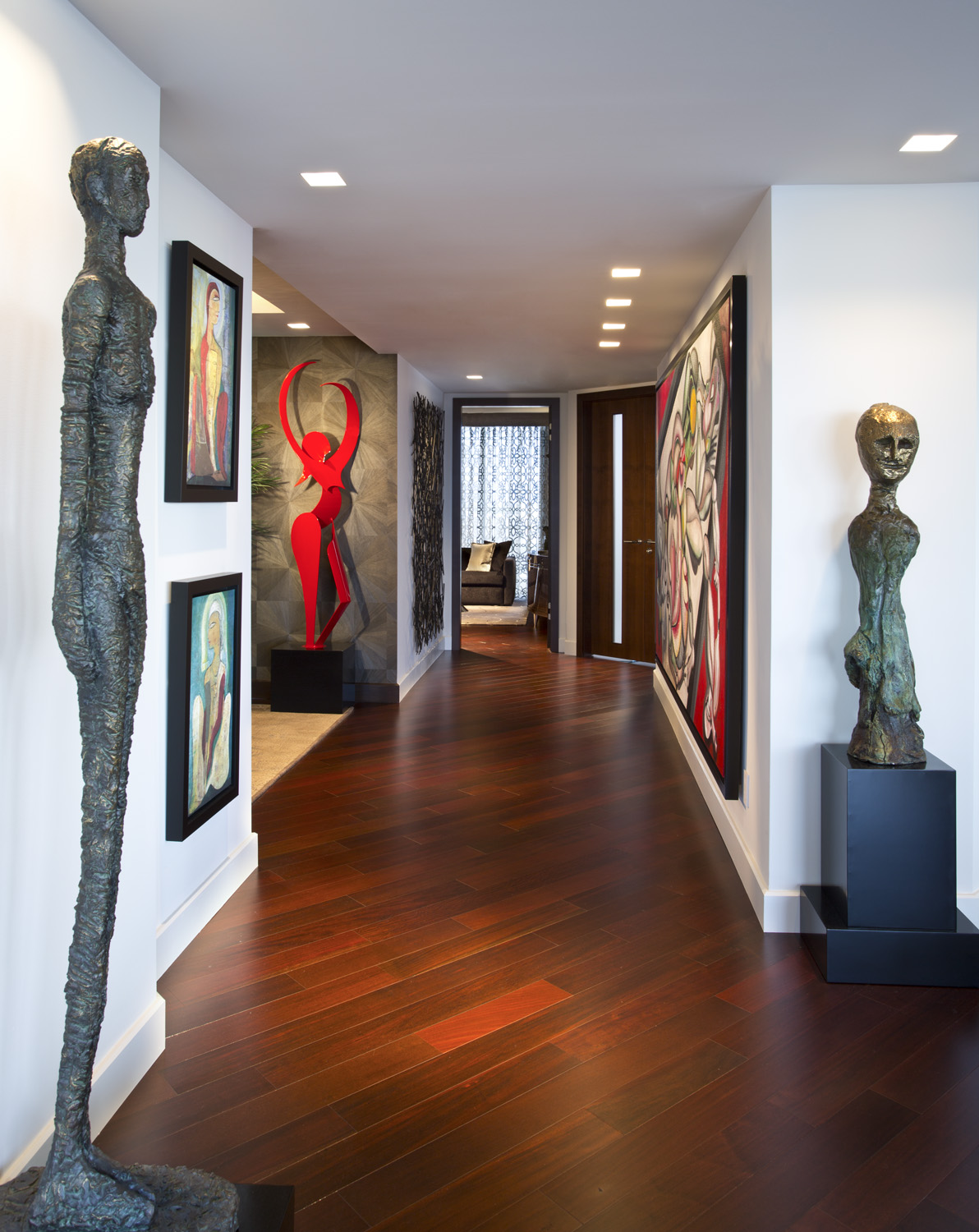 Hallway features rich dark wood flooring, wall art and free standing sculptures. by Fava Design Group
