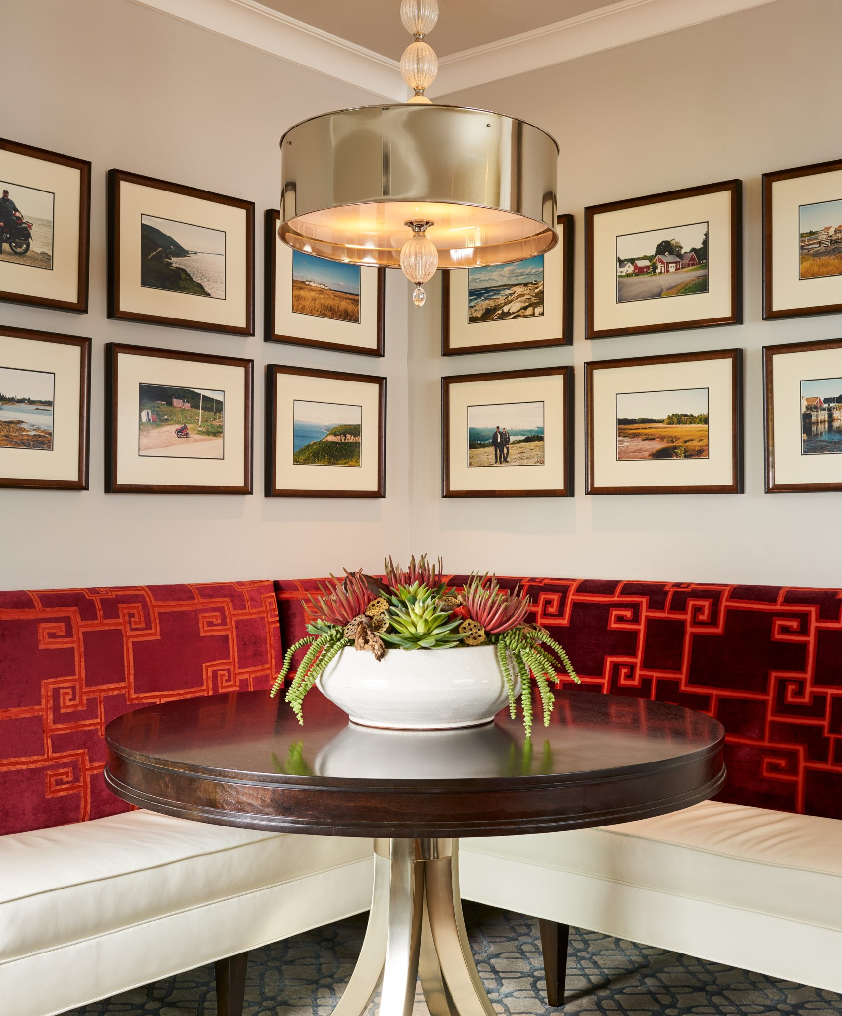 A gallery wall from the client's favorite vacations hang above the banquette. By Wesley-Wayne Interiors